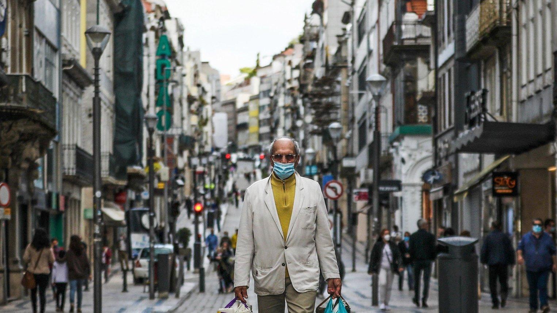 CONJUNTO DE 30 FOTOGRAFIAS SOBRE UM ANO DE ESTADO DE EMERGÊNCIA: 12-30: Foto datada de 11/05/2020: Um homem usa uma máscara protectora enquanto caminha na baixa do Porto, norte de Portugal, 11 de Maio de 2020. O comércio local, cabeleireiros, manicures, livrarias e comércio automóvel retomaram a actividade a partir de 04 de Maio, de acordo com o Plano de Descontinuação do Governo lançado na semana passada, no qual passamos de um estado de emergência para um estado de calamidade pública .JOSE COELHO/LUSA