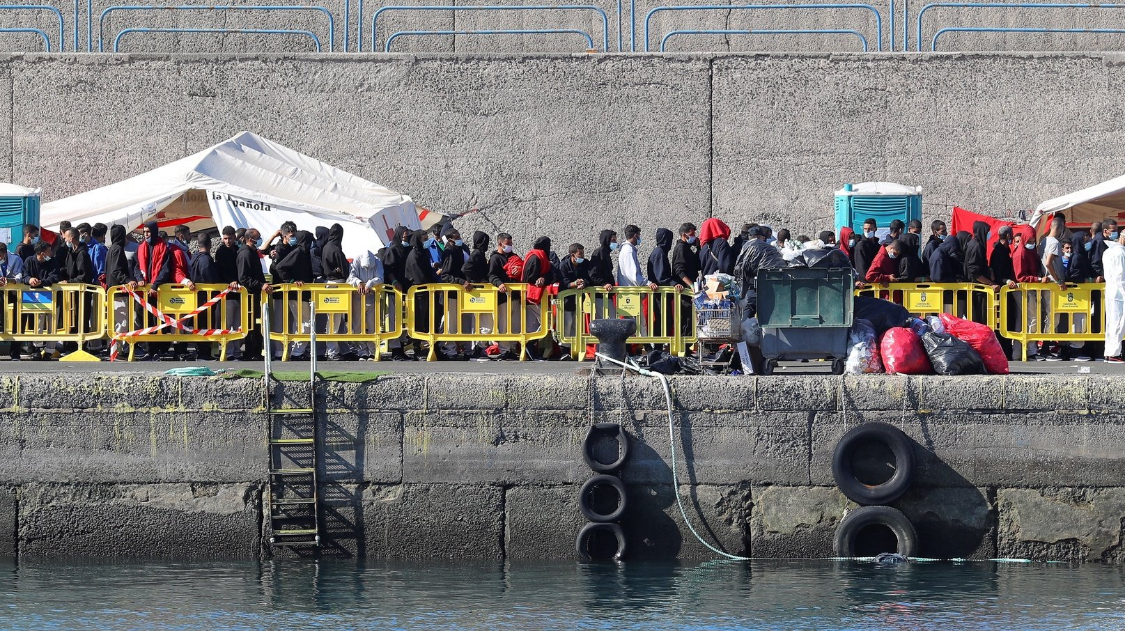 epa08807312 Migrants queue up to receive assistance at Arguineguin port in Gran Canarias, Spain, 08 November 2020. Almost 600 migrants traveling on board 21 toy boats were rescued between the late hours 07 November and the early ours of 08 November 2020. Almost 500,000 migrants have arrived to the Canary Islands throughout the year.  EPA/ELVIRA URQUIJO A.