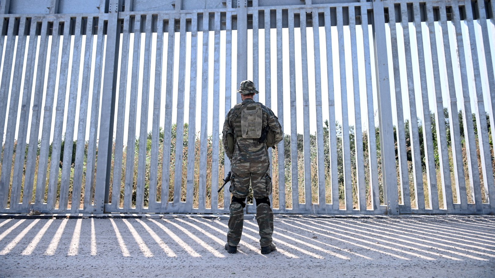 epa09440121 A soldier stands in front of a steel fence built along the Evros River in the area of Feres, at the Greek-Turkish border, Greece, 01 September 2021. The fence was built to prevent the illegal arrival of migrants into Greek territory.  EPA/DIMITRIS ALEXOUDIS