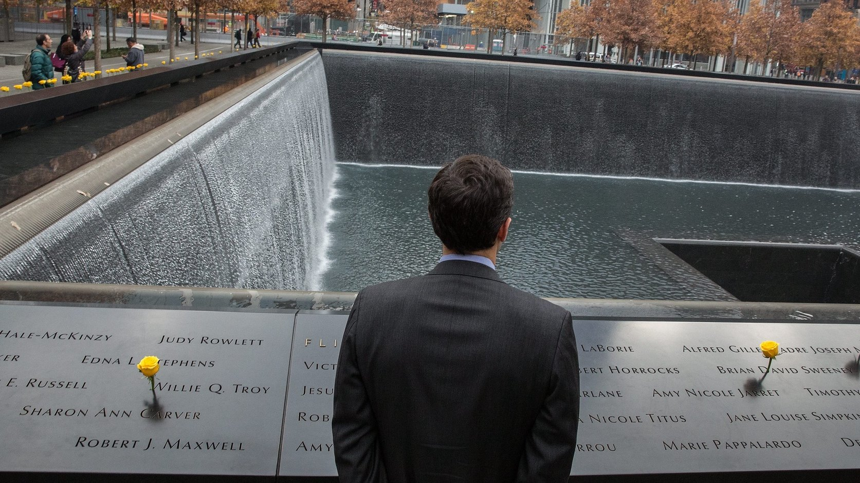 epa04485344 A passer-by pauses at the 9/11 Memorial where flowers are displayed in remembrance of Veterans Day in New York, New York, USA, 11 November 2014. Veterans Day, conciding with Armistice Day and Remembrance Day in other countries, honors those who have served in the US Armed Forces.  EPA/ANDREW GOMBERT