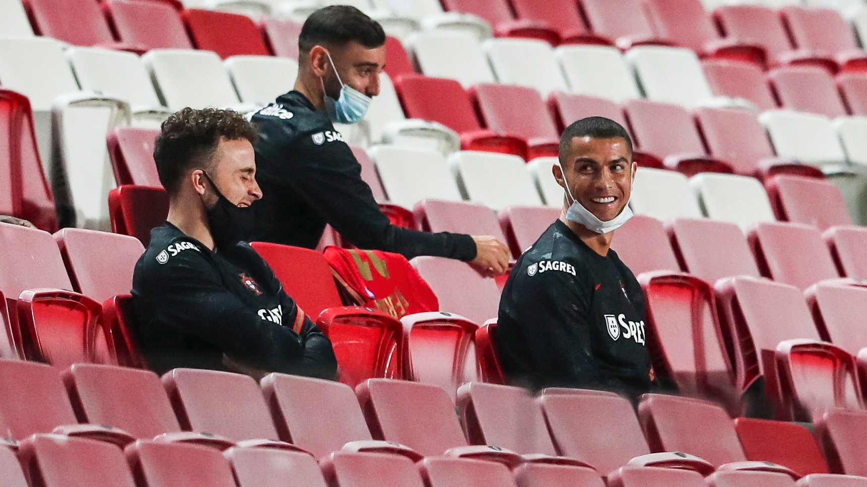 epa08814762 Portugal national team players Cristiano Ronaldo (R), Diogo Jota and Bruno Fernandes laugh in the stands prior to the friendly soccer match between Portugal and Andorra, held at Luz stadium in Lisbon, Portugal, 11 November 2020.  EPA/JOSE SENA GOULAO
