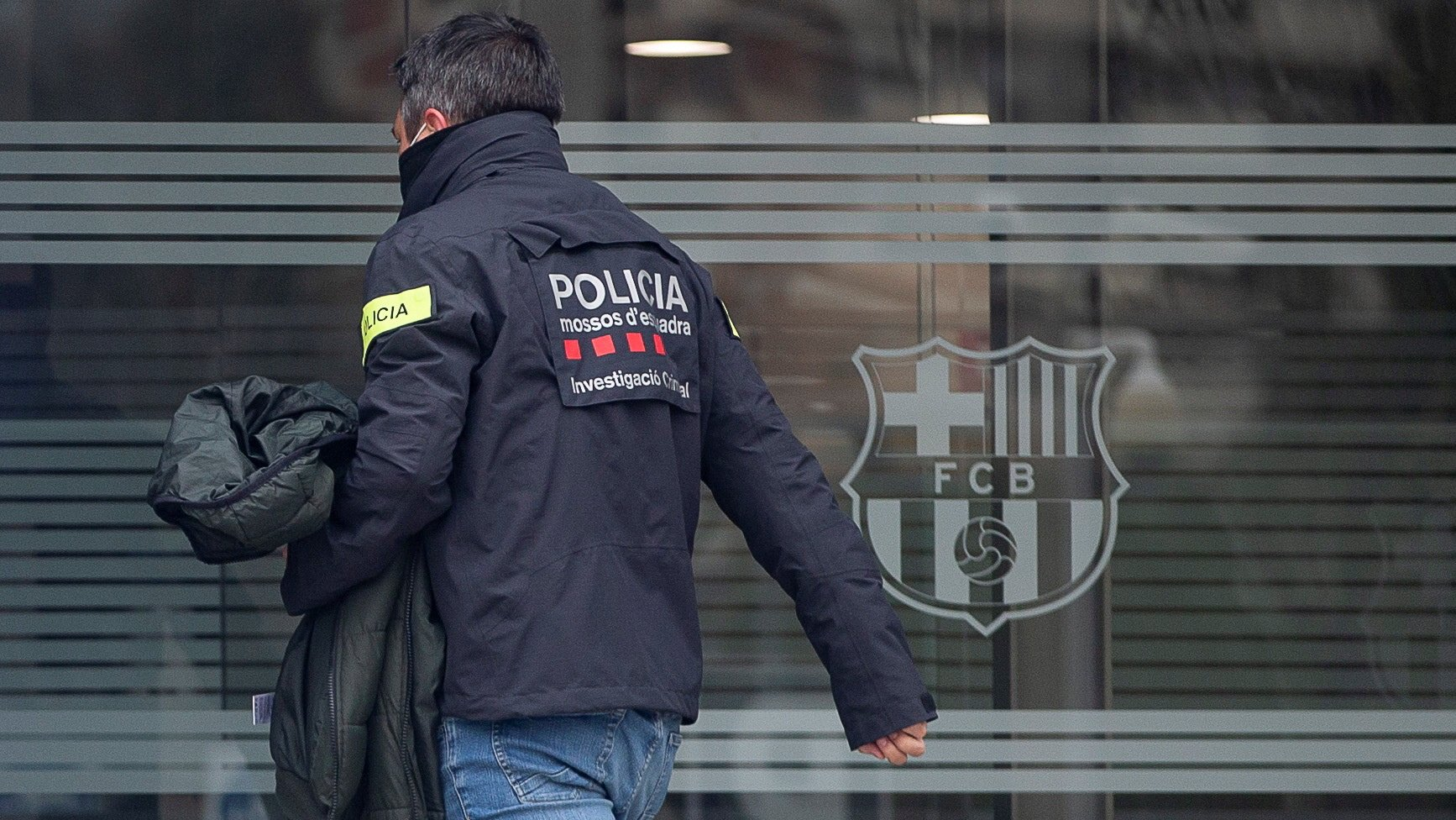 epa09045126 A members of Mossos d'Esquadra regional police's Economic Offences Unit is seen at the Spanish soccer club FC Barcelona's headquarters during a raid amid the investigation of the so-called 'BarcaGate' case, in Barcelona, Spain, 01 March 2021. Police investigates if a company, hired by the club, carried out a smear campaign against opposite players and groups to then club's board of directors. According to judicial sources FC Barcelona's former president Bartomeu, former director of the presidency area Jaume Masferrer and the current director general of the club, Ocar Grau has been arrested.  EPA/Quique Garcia