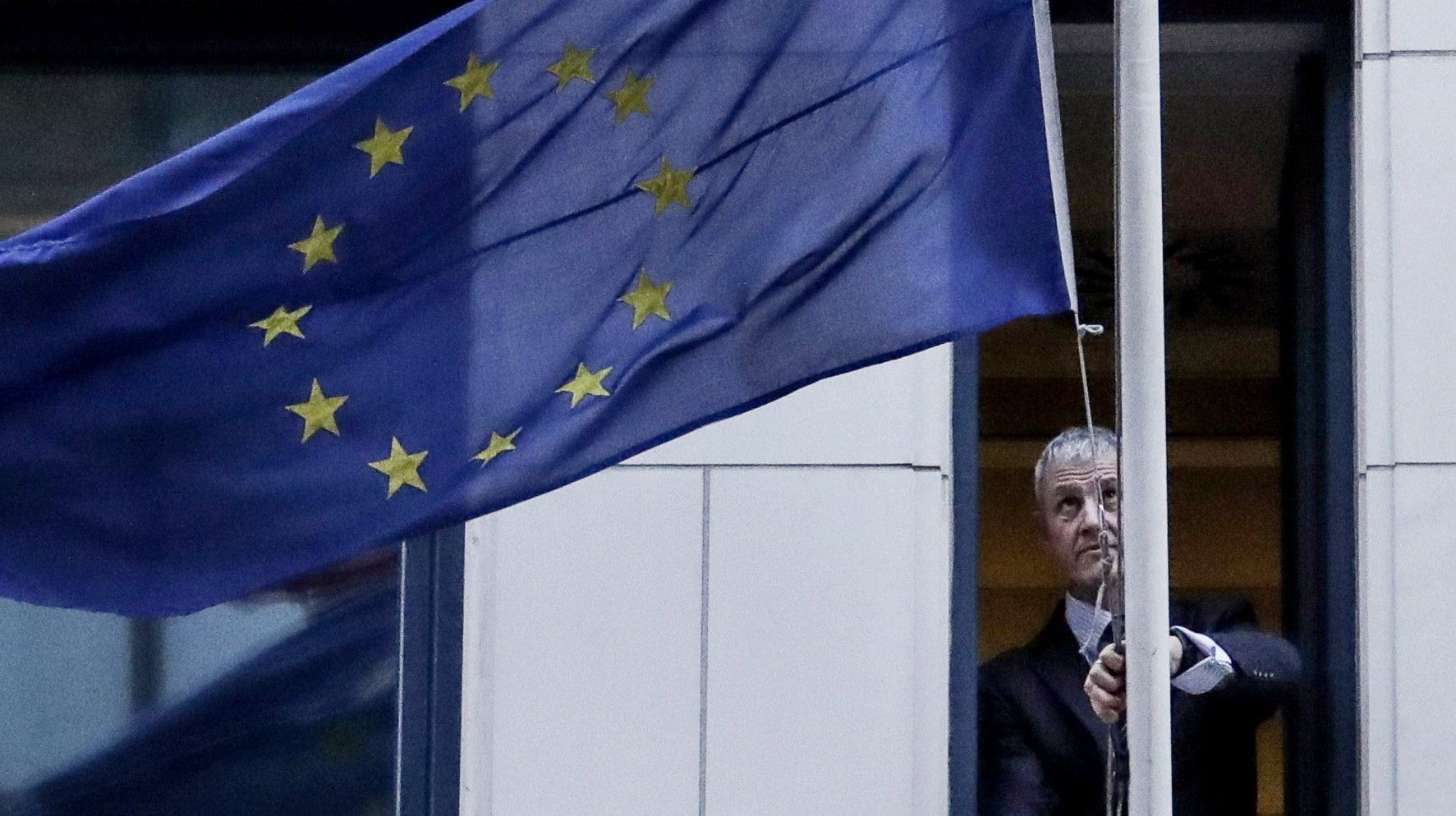 epaselect epa08182520 A man removes the European Union flag from the UK representation to the EU in Brussels, Belgium, 31 January 2020. Britain officially exits the EU on 31 January 2020, beginning an eleven month transition period.  EPA/OLIVIER HOSLET / POOL