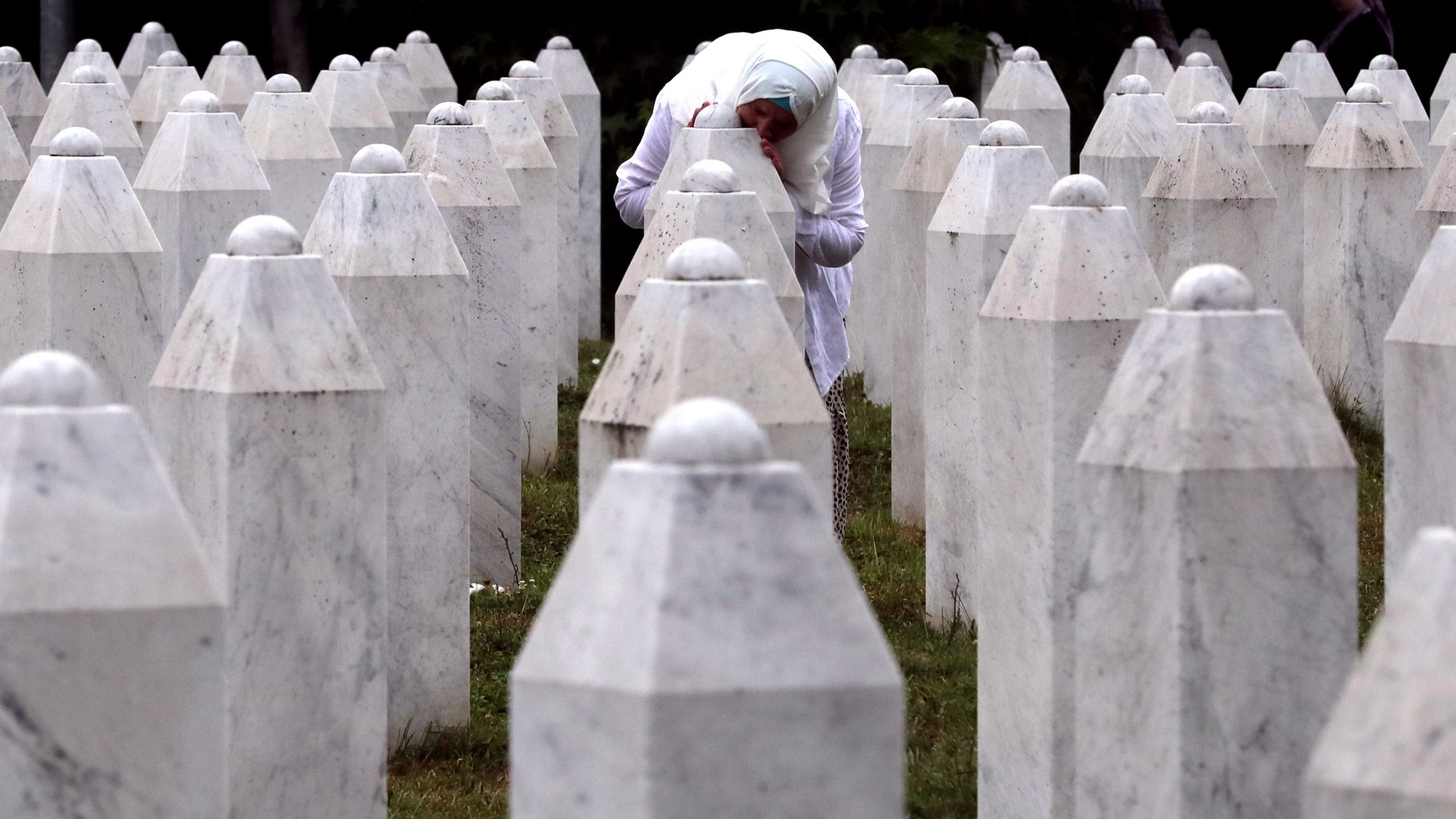 epaselect epa09336592 A Bosnian Muslim woman mourns while touching a gravestone during a funeral ceremony for nineteen newly-identified Bosnian Muslim victims, at the Potocari Memorial Center and Cemetery, in Srebrenica, Bosnia and Herzegovina, 11 July 2021. The burial was part of a memorial ceremony to mark the 26th anniversary of the Srebrenica genocide, considered the worst atrocity of Bosnia's 1992-95 war. More than 8,000 Muslim men and boys were executed in the 1995 killing spree after Bosnian Serb forces overran the town.  EPA/FEHIM DEMIR