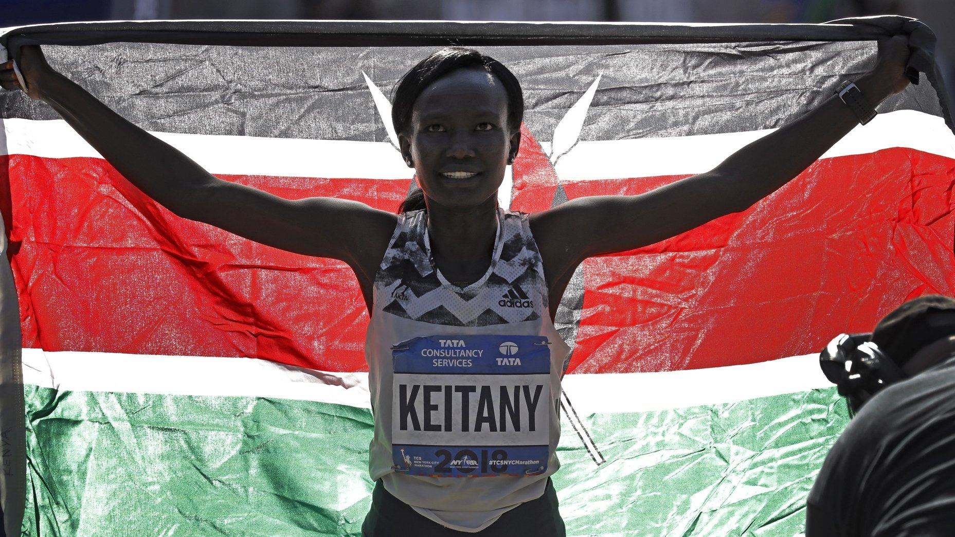 epa07141599 First place Women's finisher Mary Keitany of Kenya holds up Kenya's flag at the finish line of 2018 TCS New York City Marathon, in Central Park, New York, New York, USA, 04 November 2018.  EPA/PETER FOLEY