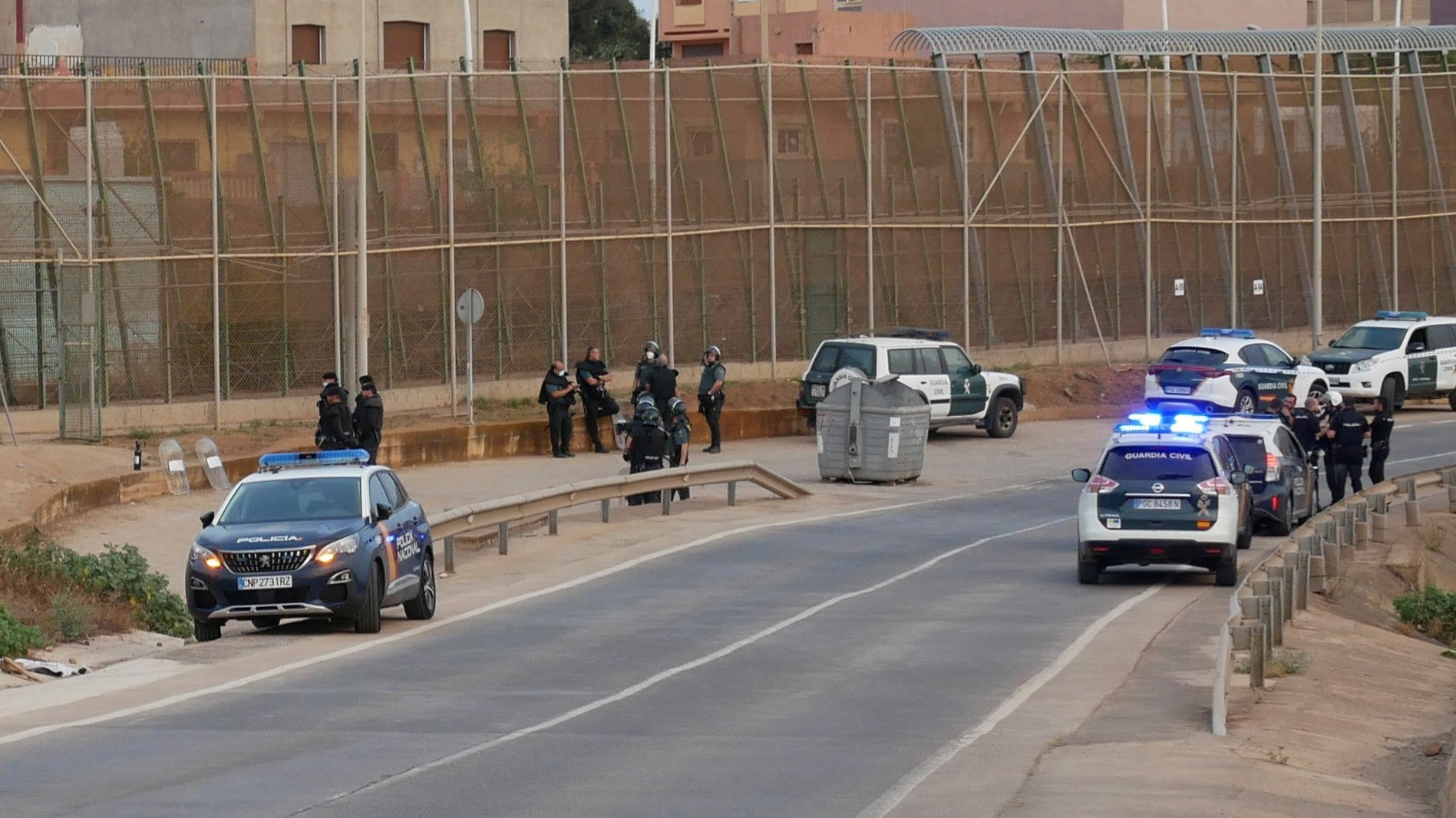 epa09363852 Spanish security forces members stand guard next to the border fence with Morocco after several migrants managed to jump the border fence and reach Spain, in Melilla, a Spanish enclave in northern Africa, 25 July 2021. Several migrants reached Spain on the early morning, the fifth such incident at the border with Morocco in the last two weeks.  EPA/PAQUI SANCHEZ