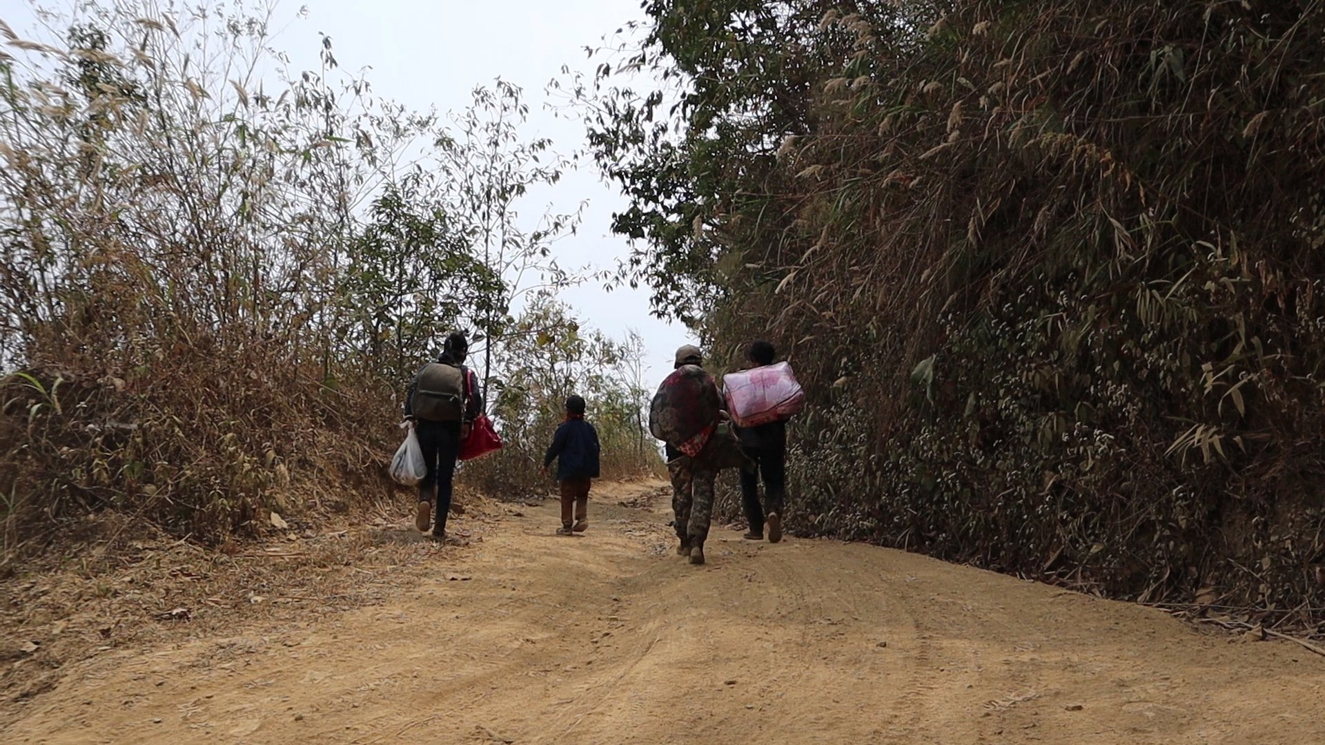 epa09098337 A small group of refugees from Myanmar carrying a few belongings after they crossed the border near a small village at an undisclosed location at the border between India and Myanmar to seek shelter in the area of Mizoram, India, 20 March 2021 (issued 26 March 2021). Many people from Myanmar crossed the border to India after the February 2021 military coup. Against all orders by the Indian government, villagers along the border and members of the Young Mizo Association (YMA), a non-governmental organization of India's northeastern state of Mizoram, are playing the role of a 'Good Samaritan' by sheltering Myanmarese seeking refuge in India. Among the refugees are many firemen and police personnel, who defied the army's forcefully order to stop the civil disobedience movement (CDM) protest across the Chin Hills state of Myanmar.  EPA/SANGZUALA HMAR