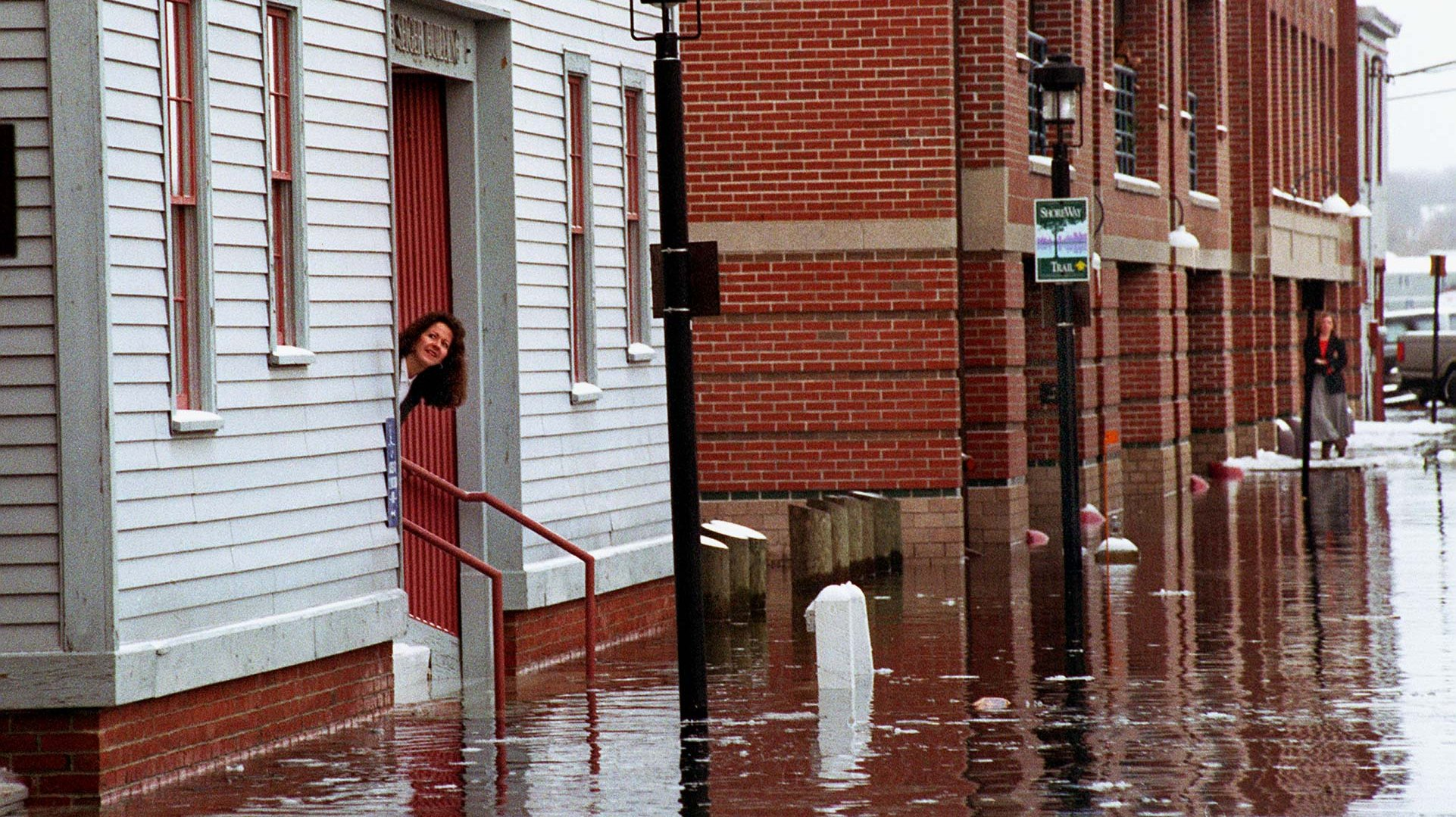 A worker peaks out the door from the Seiger Bldg. on the flooded roadway that connects Portland Pier