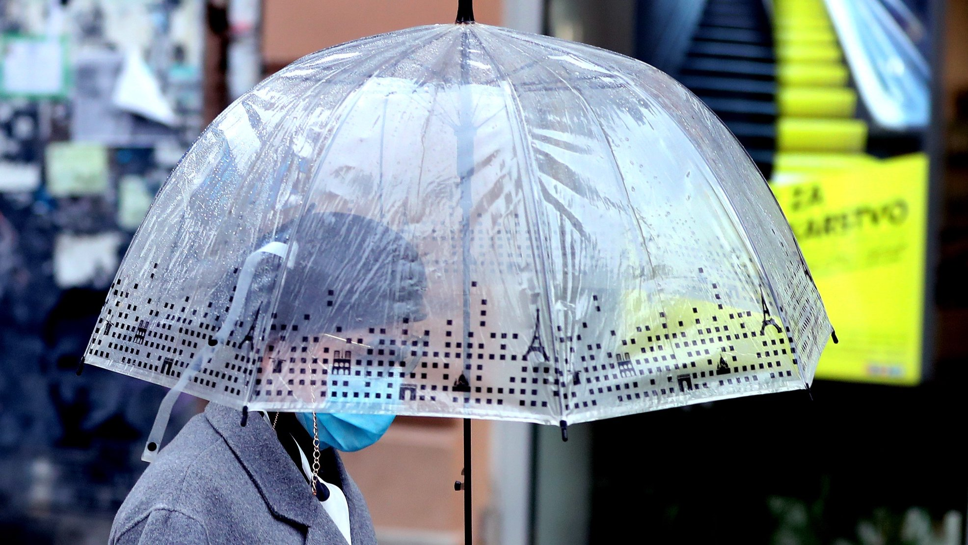 epa08830893 A woman wearing face mask walks holding an umbrella during rain in Sarajevo, Bosnia and Herzegovina, 20 November 2020.  EPA/FEHIM DEMIR
