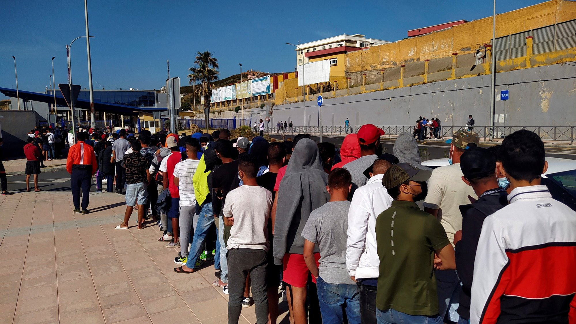 epa09242602 Moroccan migrants wait in a long queue in front of Asylum and Refuge Office at Tarajal border crossing in Ceuta, Spanish enclave in northern Africa, 02 June 2021. Most of the asylum seekers entered Ceuta on the last 17 and 18 May 2021, when some 10,000 people managed to reach Spain, mainly by sea, although some 8,000 of them came back to their country.  EPA/Reduan Dris