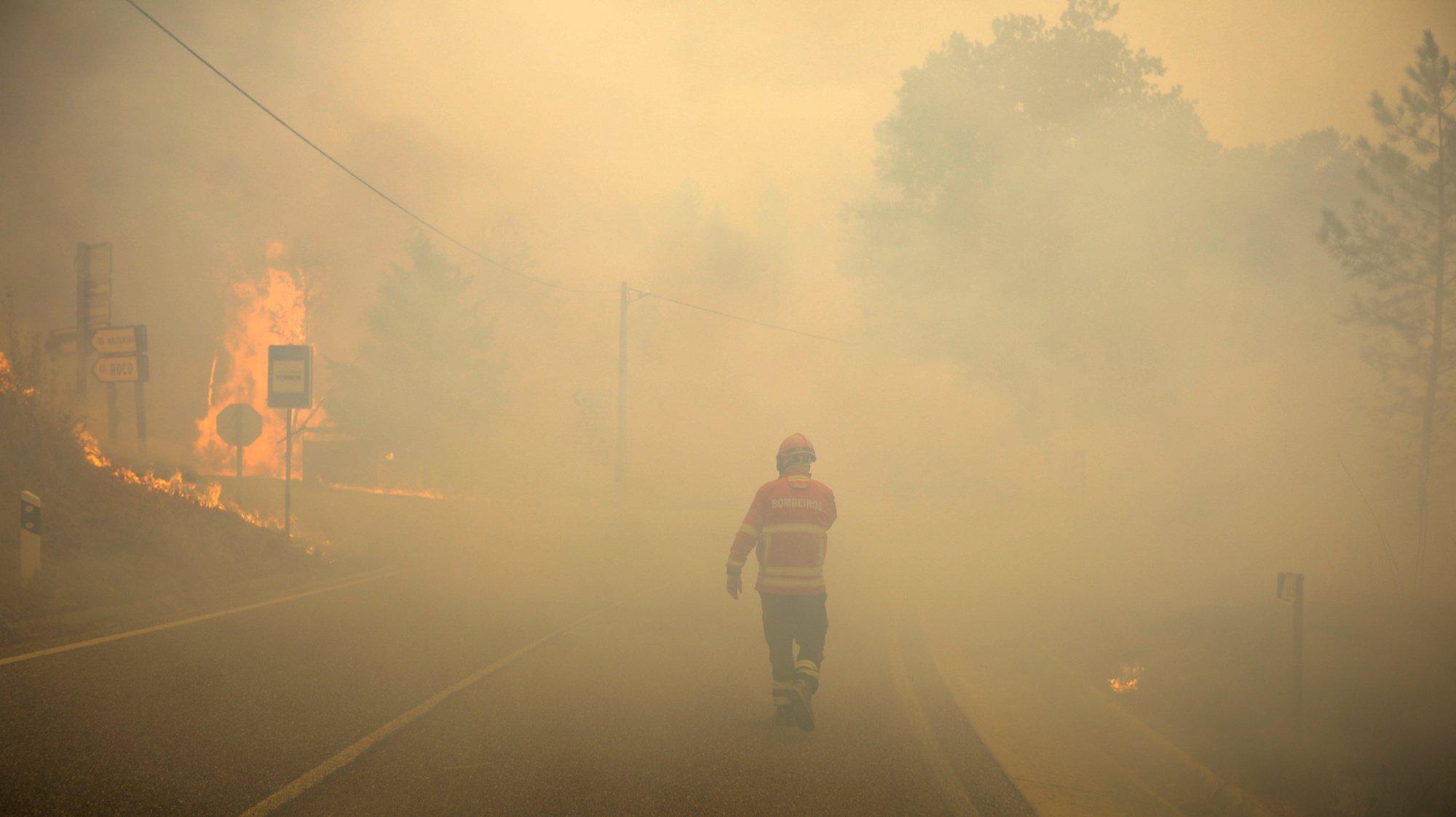 Um bombeiro observa uma frente que lavra em Oleiros, Castelo Branco, 14 de setembro de 2020. O incêndio que deflagrou em Proença-a-Nova no domingo e que lavra hoje com intensidade em Oleiros já está próximo do Rio Zêzere, afirmou hoje o presidente da Câmara. Segundo a Autoridade Nacional de Emergência e Proteção Civil estão neste momento a combater o incêndio 955 operacionais no terreno, apoiados por 315 veículos e quinze meios aéreos. PAULO CUNHA /LUSA