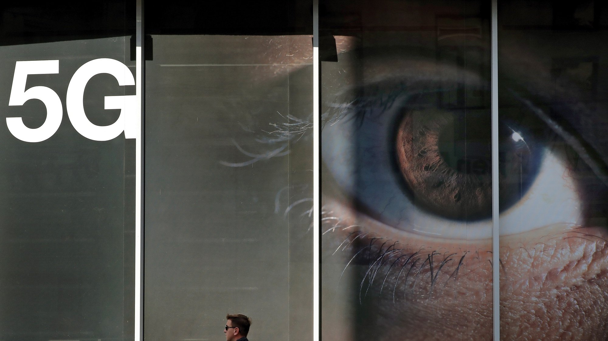 epaselect epa08757561 A Romanian man passes in front of a shop window of an Orange store that displays a huge 5G advertise banner, in Bucharest, Romania, 19 October 2020. Romania was among the first countries in the EU where local mobile communications operators launched commercial 5G services, through upgrades of 4G networks, using the radio spectrum they currently have in 2019, as The National Authority for Management and Regulation in Communications (ANCOM) failed to properly organize an auction for the rest of the frequency bands necessary for mobile operators to implement the 5G standard at the announced optimal parameters. The communication business sector is waiting for a new auction to be organized until the end of 2020. Mobile internet traffic is doubling in Romania every year.  EPA/ROBERT GHEMENT