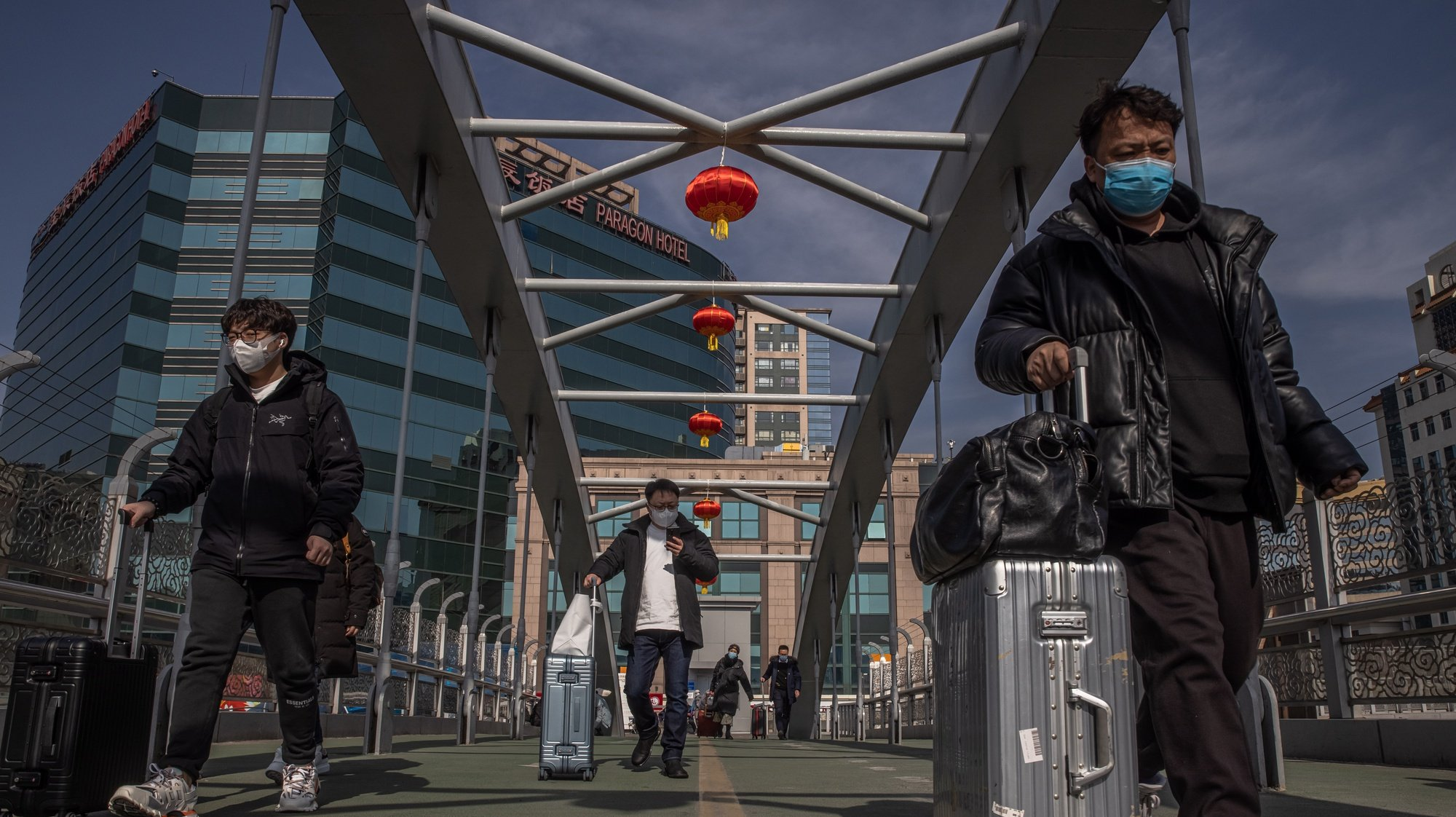 epaselect epa09000277 Chinese passengers carry their luggage and walk on a bridge towards the Beijing Railway Station before the upcoming Chinese Lunar New Year, in Beijing, China, 10 February 2021. The Lunar New Year, also known as Spring Festival, falls on 12 February 2021, marking the beginning of the Year of the Ox. Authorities in China urged people not to travel to their hometowns during Lunar New Year due to the COVID-19 outbreaks in the country.  EPA/ROMAN PILIPEY