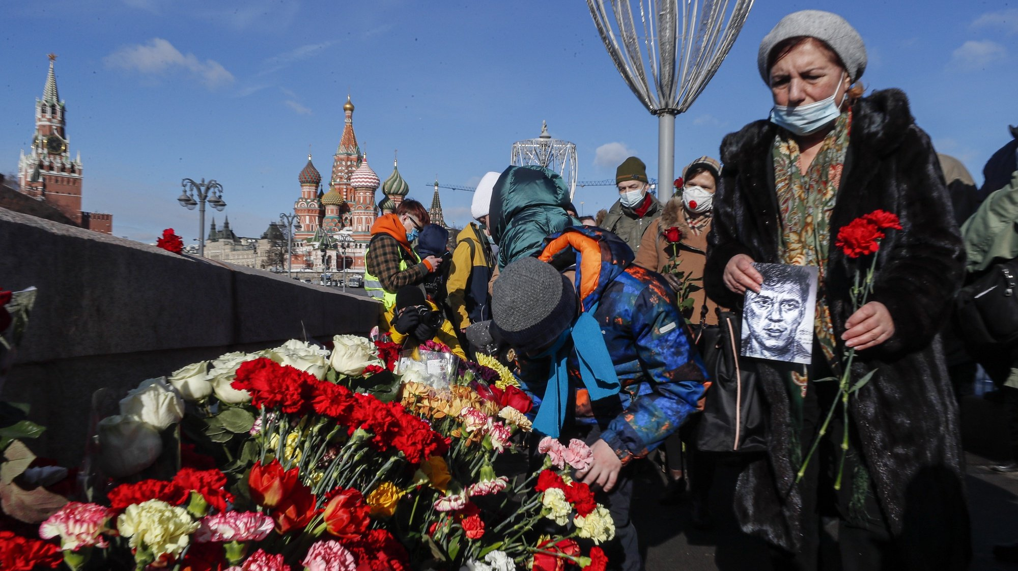epa09039796 People lay flowers at the site where Russian opposition politician Boris Nemtsov died during an event marking the sixth anniversary of his assassination, in Moscow, Russia, 27 February 2021. Boris Nemtsov was killed on 27 February 2015 by suspected Chechen hitmen on a bridge in front of the Kremlin.  EPA/SERGEI ILNITSKY
