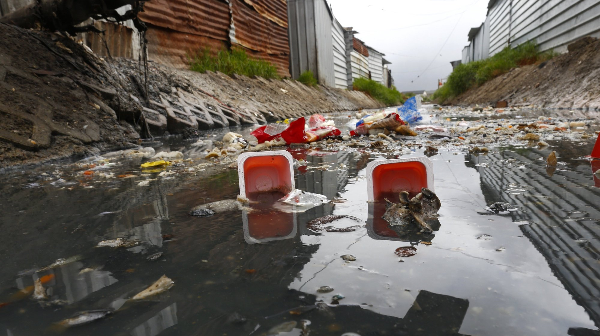 epa06602747 A general view of garbage in a highly polluted river next to shack homes in Masiphumelele, Cape Town, South Africa, 14 March 2018. Rapid urbanization and a national government that has not provided enough infrastructure in high density neighborhoods like Masiphuumelele are two of the major factors environmentalists cite contributing to the polluting of urban rivers. Environmental activists globally observe on 14 March annually the International Day of Action for Rivers with the aim of raising awareness around issues concerning the world's water ways.  EPA/NIC BOTHMA