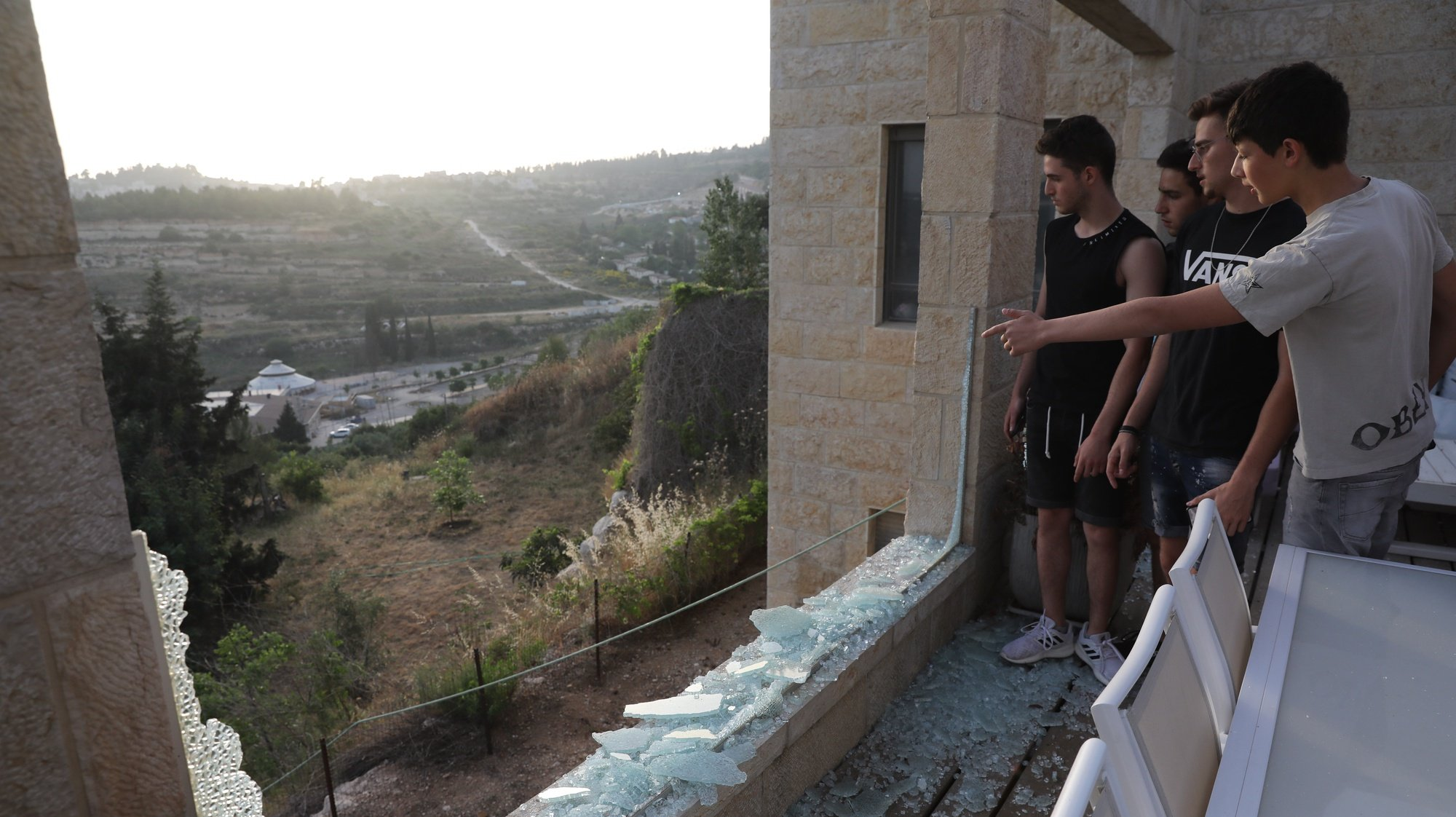 epa09189820 Israelis look out from a broken window in their home, as a result from missile fired from Gaza Strip, at the village of Beit Nekufa near Jerusalem, Israel, 10 May 2021 as tensions rise between Israel and Palestinians.  EPA/ABIR SULTAN