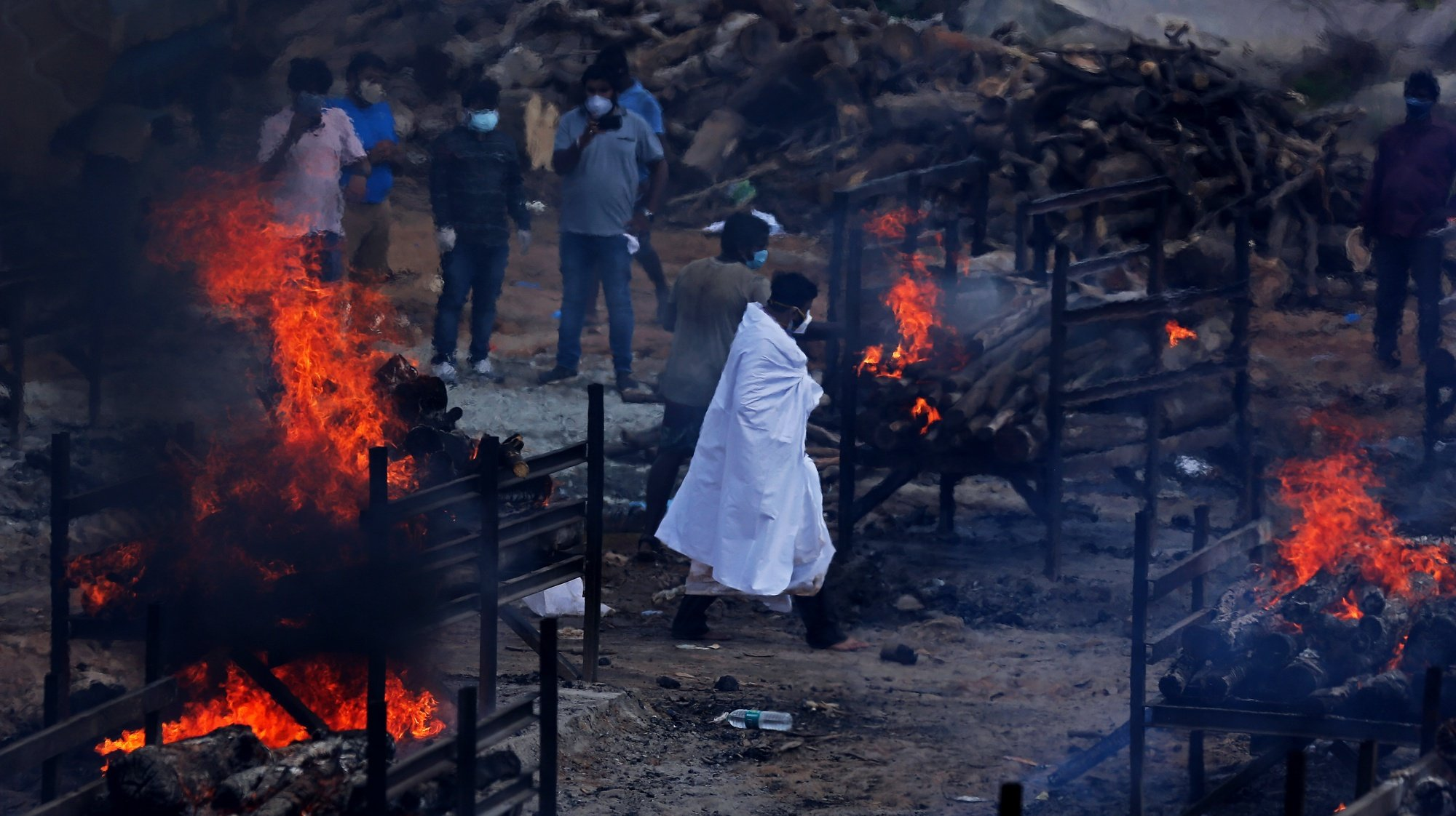 epaselect epa09209124 Funeral pyres for COVID-19 victims burn during a mass funeral at a makeshift cremation ground at Giddenahalli in the outskirts of Bangalore, India, 18 May 2021. India surpassed 25 million cases of the coronavirus on 18 May since the start of the pandemic, despite a decline in infections in recent days, while also recording a new daily record of 4,329 deaths. The country registered 263,533 infections in the last 24 hours, according to data from the Indian Ministry of Health, the lowest number in a month after India reported a record of over 400,000 cases everyday two weeks ago. The total Covid-19 toll now stands at 25.2 million cases - second highest after the United States - and 278,719 deaths - third highest after the US and Brazil.  EPA/JAGADEESH NV