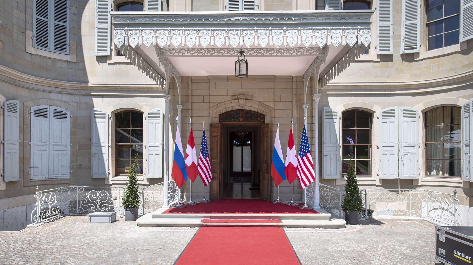 epa09273033 Flags of the US, Russia and Switzerland photographed in front of the entrance of the villa La Grange, one day prior to the US - Russia summit in Geneva, Switzerland, 15 June 2021. The meeting between US President Joe Biden and Russian President Vladimir Putin is scheduled in Geneva for 16 June 2021.  EPA/PETER KLAUNZER