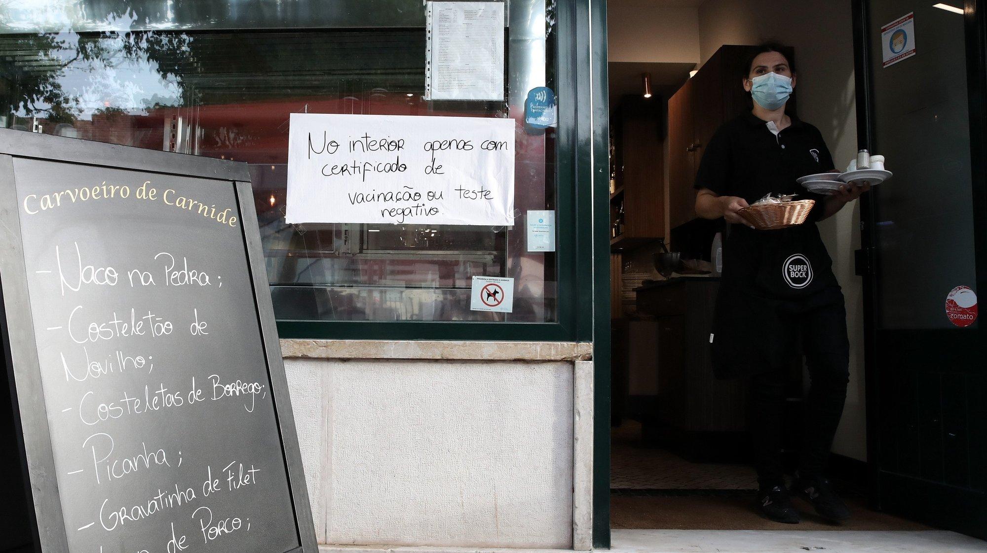 Aviso sobre certificado digital ou teste à entrada de um restaurante em Lisboa, após o Governo decreta que os restaurantes em concelhos de risco elevado ou muito elevado – um total de 60 – passam a ter de exigir certificado digital ou teste negativo à covid-19 a partir das 19:00 de sexta-feira e aos fins de semana para refeições no interior, Lisboa, 10 de julho de 2021. As pessoas em esplanadas que precisarem de entrar nos restaurantes para acesso aos serviços comuns, como instalações sanitárias, ou para efetuarem pagamento, estão dispensadas de apresentar um teste negativo à covid-19 ou o certificado digital. MANUEL DE ALMEIDA/LUSA