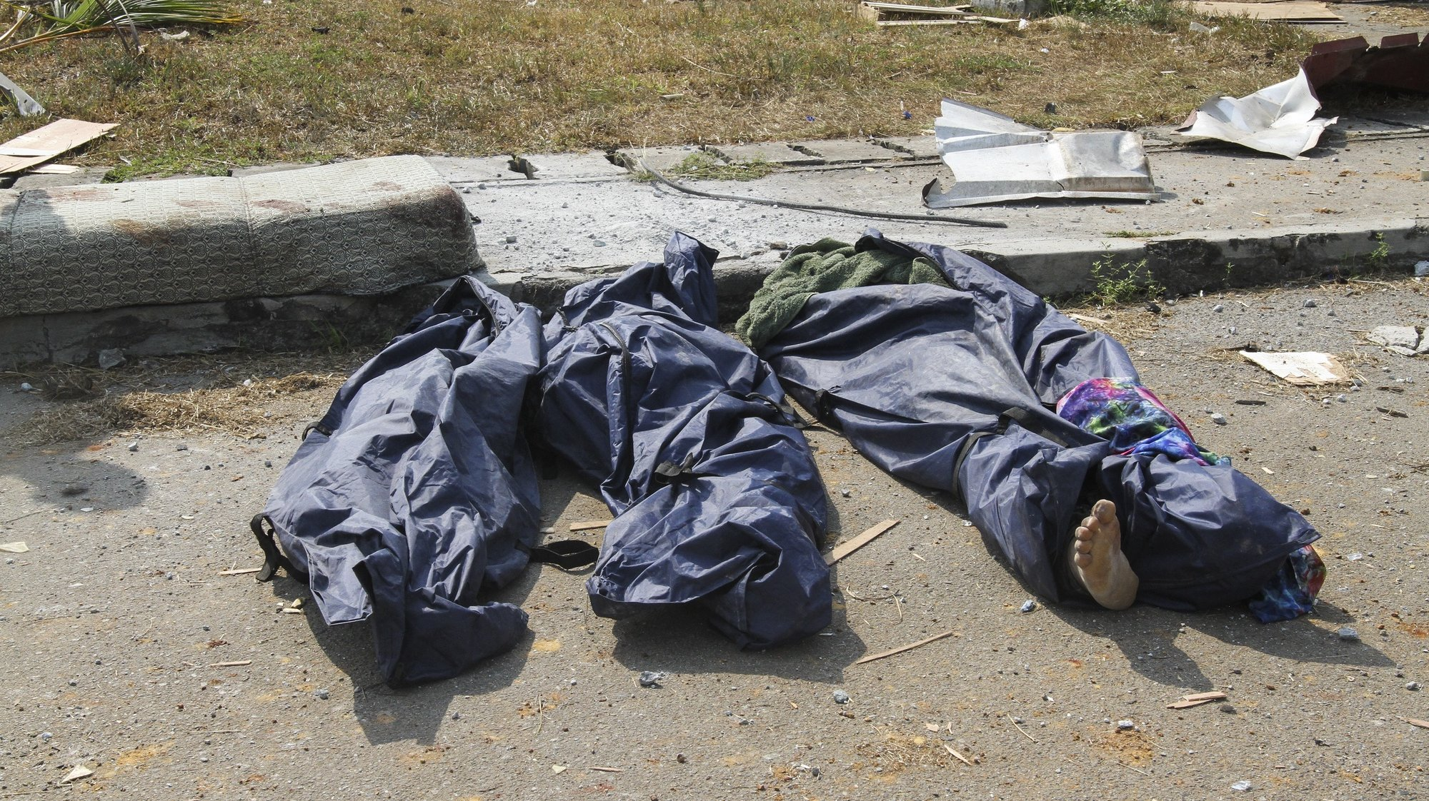 epa09062161 Bodies in body bags at the scene of the aftermath of an explosion in Bata, Equatorial Guinea, 08 March 2021. According to President Teodoro Obiang Nguema huge damage occured when a dynamite storage facility exploded in the port city of Bata on 07 March 2021. According to the Equatorial Guinea health ministry there is an initial count of 20 dead and 420 injured people are being treated in hospitals.  EPA/JOSE LUIS ABECARA AGUESOMO ATTENTION EDITORS: GRAPHIC CONTENT