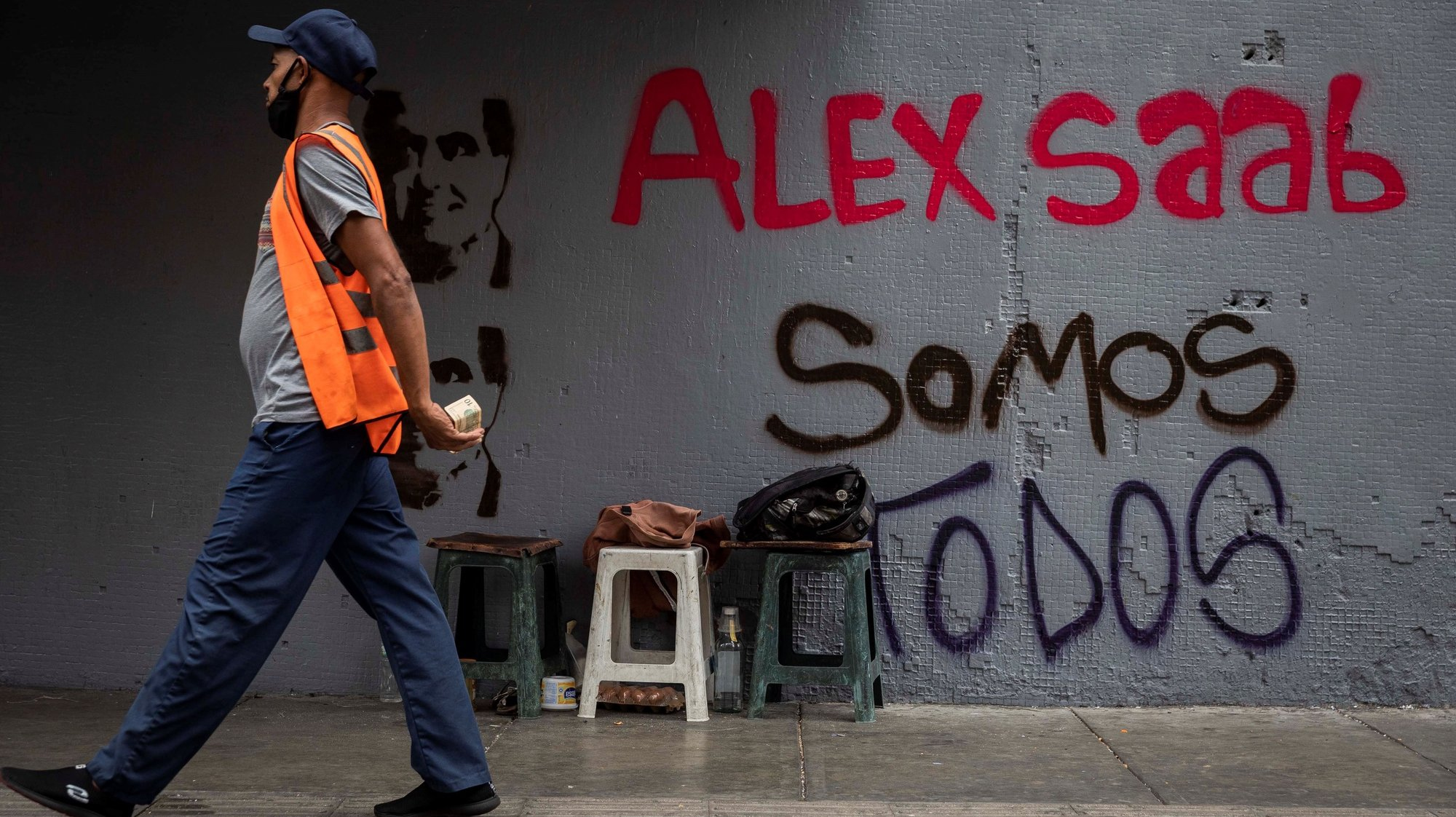 epa09030458 A man walks in front of a graffiti that reads 'We all are Alex Saab', in Caracas, Venezuela, 22 February 2021. Chavista supporters have painted murals in the Venezuelan capital to show their support and request the release of Alex Saab, a Colombian businessman detained in Cape Verde and whom the United States is asking for extradition by accusing him of being a front man for the president of Venezuela, Nicolas Maduro.  EPA/Rayner Pena