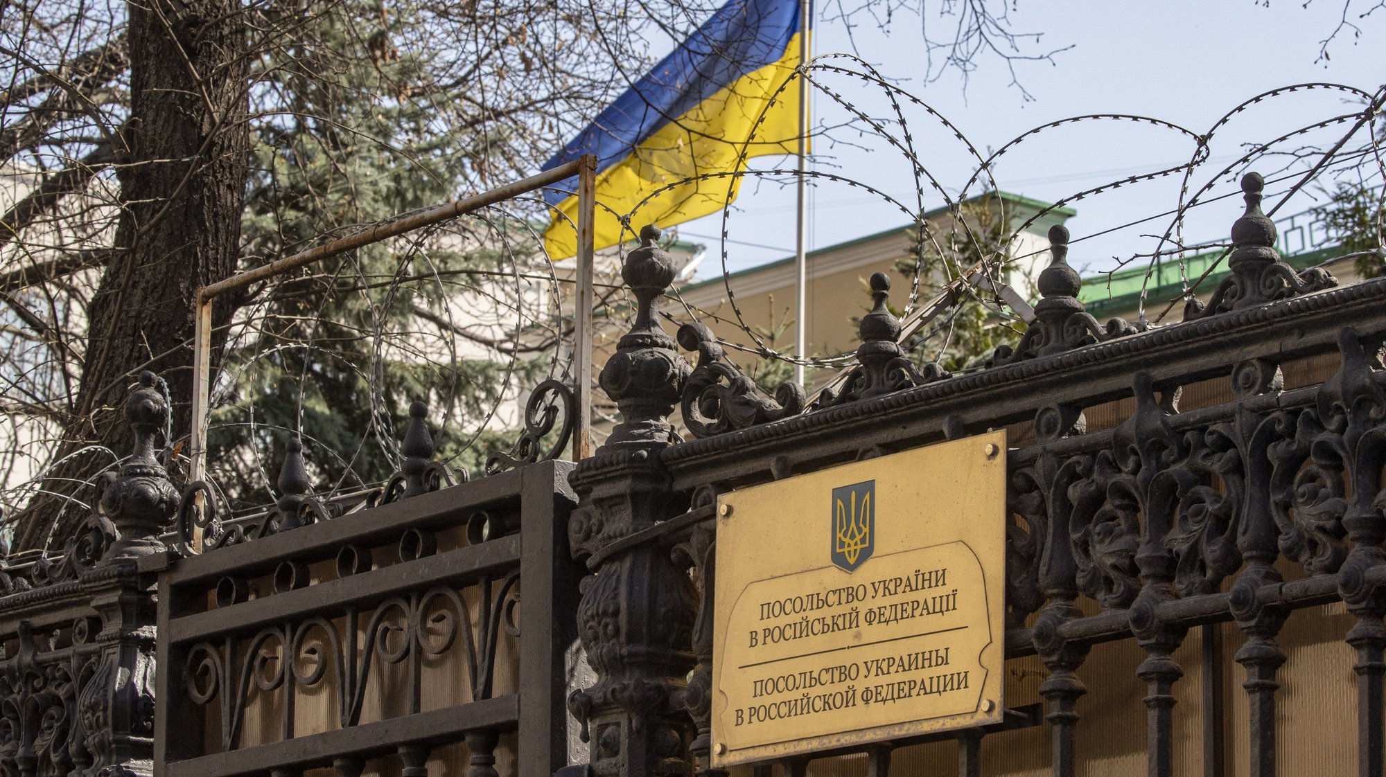 epa09141100 An Ukrainian National flag waves behind the fence of the Ukrainian embassy in Moscow, Russia, 17 April 2021. The Federal Security Service of the Russian Federation announced that Ukrainian consul general Alexander Sosonyuk, on 16 April in St. Petersburg, was detained red-handed while receiving information of a classified nature during a meeting with a Russian citizen.  EPA/SERGEI ILNITSKY