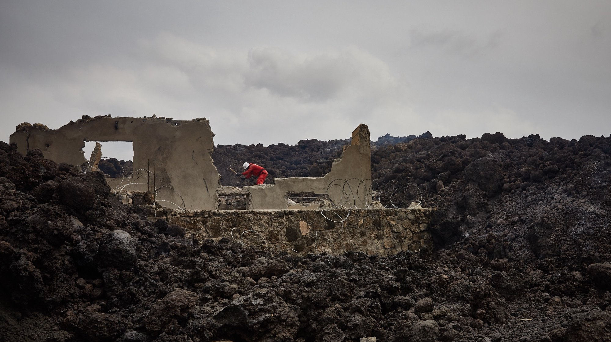epa09227823 Workers begin to clear piles of lava in the aftermath of a volcanic eruption in Goma, North Kivu, Democratic Republic of Congo, 25 May 2021. One of the planets most active volcanoes Mount Nyiragongo in eastern Democratic Republic of Congo erupted 22 May 2021. According to local journalists, aftershocks from the Nyiragongo volcanic eruption continue in the town of Goma. According to the United Nations children's agency (UNICEF) 25 May 2021 more than 100 children are missing after having been separated from their parents. Foreign countries, like the United Kingdom, have warned their nationals through their embassies of the continuation of seismic activity and cannot rule out further fissures or lava flow.  EPA/HUGH KINSELLA CUNNINGHAM