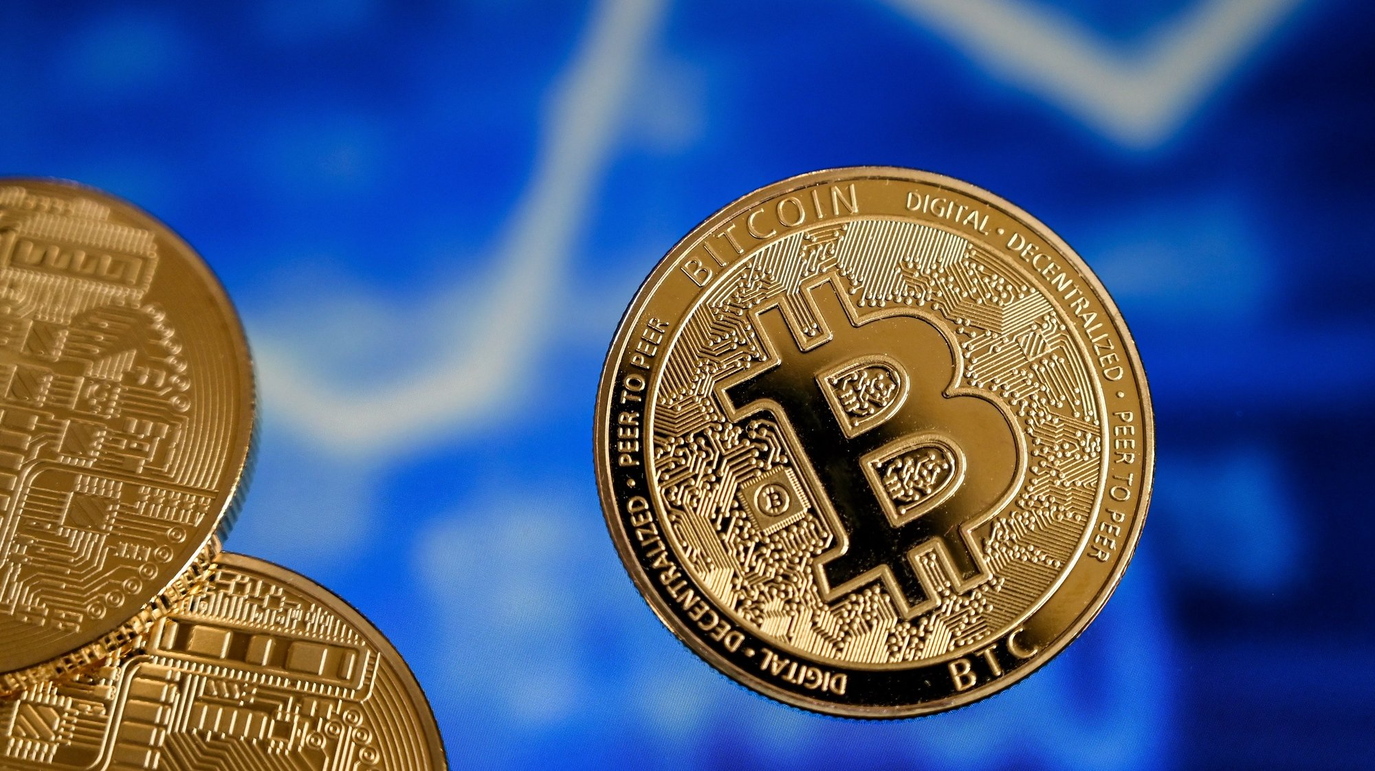 epa09018336 A bitcoin reflects in front of a monitor showing a stock barometer in Duesseldorf, Germany, 17 February 2021. For the first time, the cryptocurrency Bitcoin has exceeded the mark of 50,000 dollars. Most recently, it became known that Elon Musk, CEO of the US electric car manufacturer Tesla, is said to have invested 1.5 billion dollars in Bitcoin. In recent weeks, he had boosted Bitcoin as well as other Internet currencies with positive news via the short message service Twitter. Credit card provider MasterCard also announced that it would open its payment network to cryptocurrencies. Visa plans to help banks introduce trading with Bitcoin and other cryptocurrencies by launching software with API access.  EPA/SASCHA STEINBACH