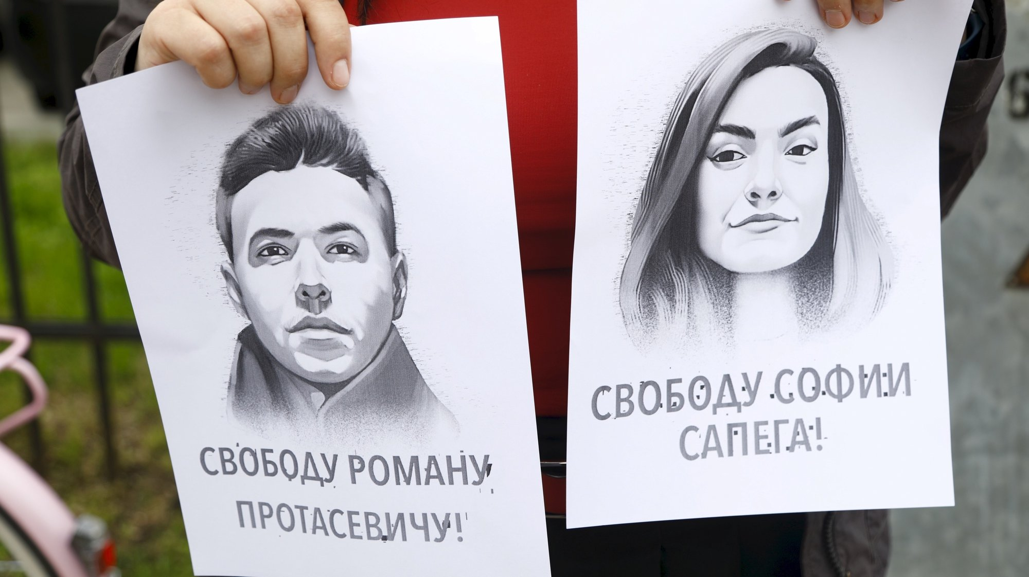 epa09226579 A woman holds a portrait of opposition journalist Roman Protasevich and his girlfriend Sofia Sapega during a protest of solidarity with Roman Protasevic at the Belarusian embassy in Riga, Latvia, 25 May 2021. Belarus' opposition journalist Roman Protasevich was detained by Belarusian Police on 23 May on a Ryanair flight from Athens to Vilnius, that was forced to land in Minsk.  EPA/TOMS KALNINS