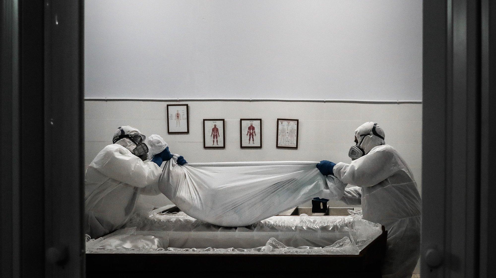 (04/23) Funcionários de uma agência funerária seguram o corpo de uma mulher vítima de covid-19, na Amadora, 29 de janeiro de 2021. Esta semana Portugal ultrapassou as 300 mortes diárias por covid-19, um novo máximo desde o início da pandemia. (ACOMPANHA TEXTO DA LUSA DO DIA 30 DE JANEIRO DE 2021). MÁRIO CRUZ/LUSA