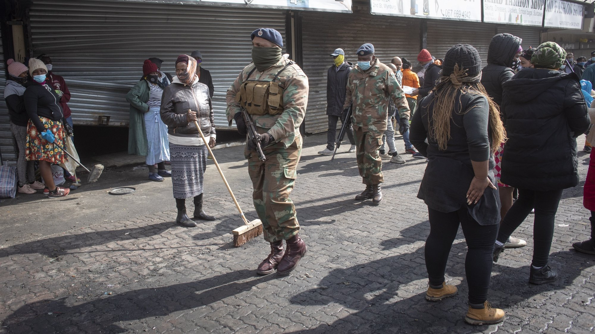epa09345807 Soldiers from the South African Defense Force (SANDF) patrol the streets while local residents clean up the streets and local businesses after looting incidents in department stores and shops in Alexandra township, Johannesburg, South Africa, 15 July 2021. Days of looting and violence in both Johannesburg and Durban have caused billions of Rands of damage as an estimated 200 shopping malls where affected.  EPA/KIM LUDBROOK