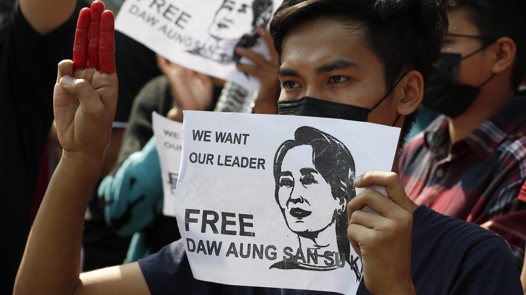 epa08993326 Protesters hold portraits of detained Myanmar State Counselor Aung San Suu Kyi reading 'We Want Our Leader Free' and flash the three-finger salute, a symbol of resistance, during a protest against the military coup in Yangon, Myanmar, 07 February 2021. Thousands of people took to the streets of Yangon, Myanmar's biggest city, for a second day of mass protests against the military coup amid internet shut down imposed by military rulers. Myanmar's military seized power and declared a state of emergency for one year after arresting State Counselor Aung San Suu Kyi and Myanmar president Win Myint in an early morning raid on 01 February.  EPA/NYEIN CHAN NAING