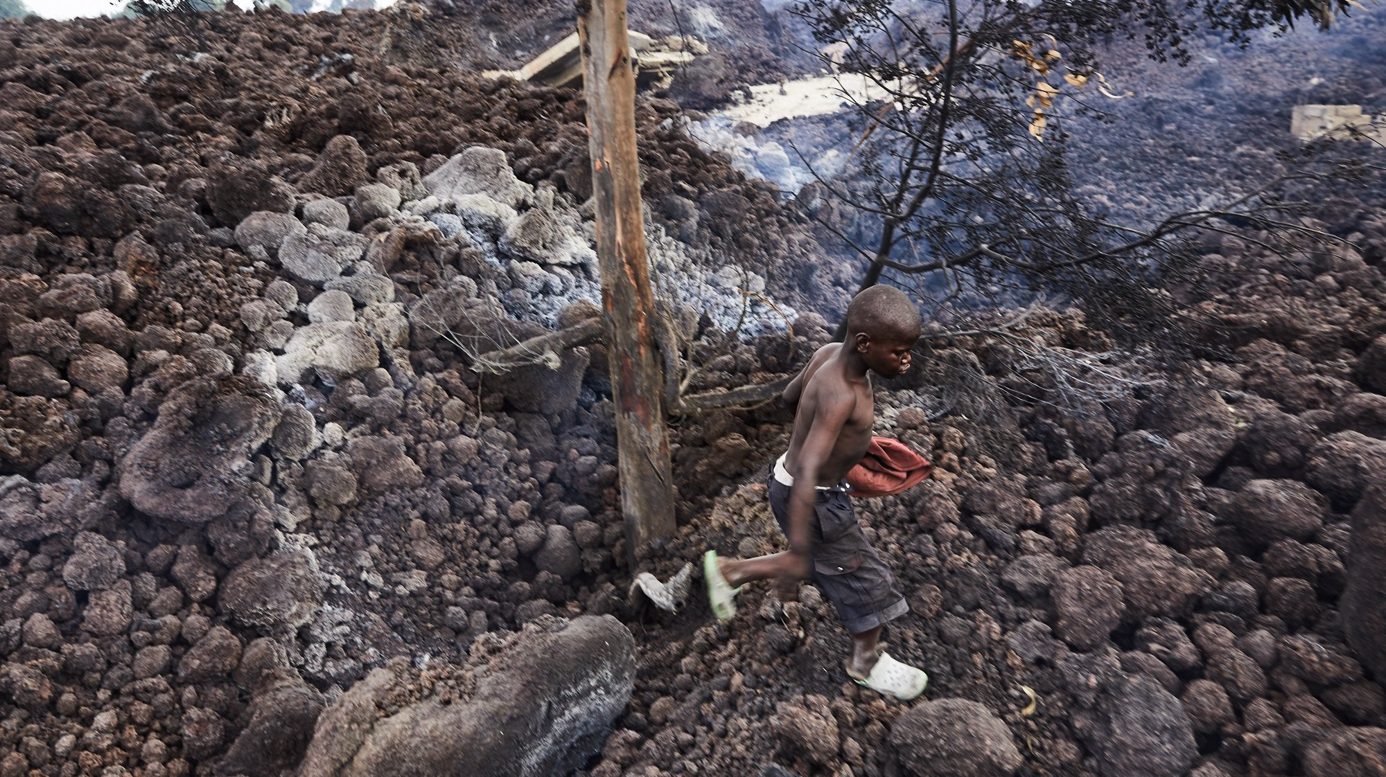 epa09227820 A Congolese boy in the neighbourhood of Buhene walks on piles of lava in the aftermath of a volcanic eruption in Goma, Democratic Republic of Congo, 25 May 2021. One of the planets most active volcanoes Mount Nyiragongo in eastern Democratic Republic of Congo erupted 22 May 2021. According to local journalists, aftershocks from the Nyiragongo volcanic eruption continue in the town of Goma. According to the United Nations children's agency (UNICEF) 25 May 2021 more than 100 children are missing after having been separated from their parents. Foreign countries, like the United Kingdom, have warned their nationals through their embassies of the continuation of seismic activity and cannot rule out further fissures or lava flow.  EPA/HUGH KINSELLA CUNNINGHAM