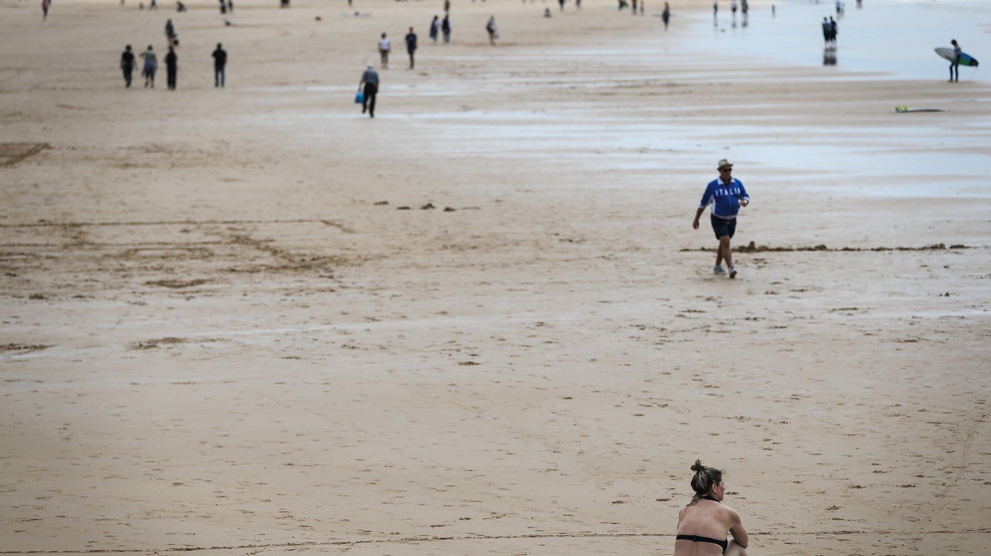 Uma mulher apanha sol no dia em que se assinala a abertura da época balnear na praia de Carcavelos, em Cascais, 15 de maio de 2021.  RODRIGO ANTUNES/LUSA