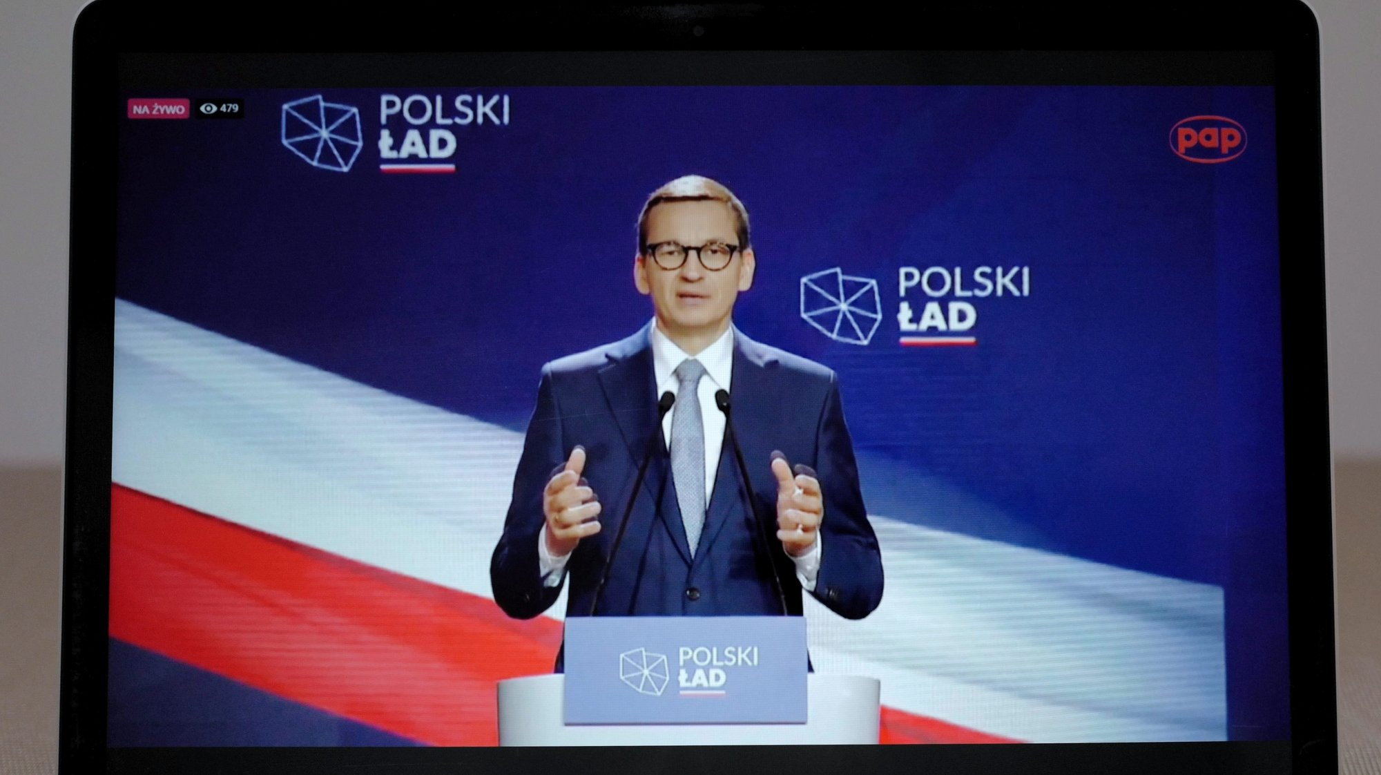 epa09242809 Polish Prime Minister Mateusz Morawiecki presents 10 key points of the government's Polish New Deal plan to revive the national economy after the Covid-19 pandemic during a speech watched on a screen in Warsaw, Poland, 02 June 2021. The plan, which envisages major investment in public infrastructure along with overhauls of the tax and healthcare systems, was made public last month but Mateusz Morawiecki added more details during a presentation on 02 June 2021.  EPA/Mateusz Marek POLAND OUT