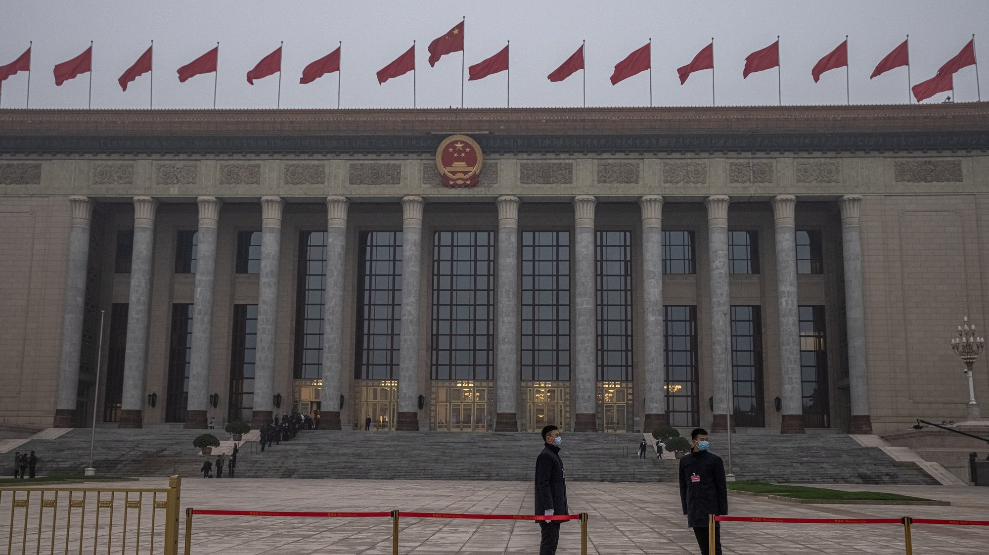 epa09053086 Security officials wearing protective face masks stand guard in front of the Great Hall of the People prior to the opening session of the National People's Congress (NPC), in Beijing, China, 05 March 2021. China holds two major annual political meetings, The National People's Congress (NPC) and the Chinese People's Political Consultative Conference (CPPCC) which run alongside and together known as 'Lianghui' or 'Two Sessions'.  EPA/ROMAN PILIPEY