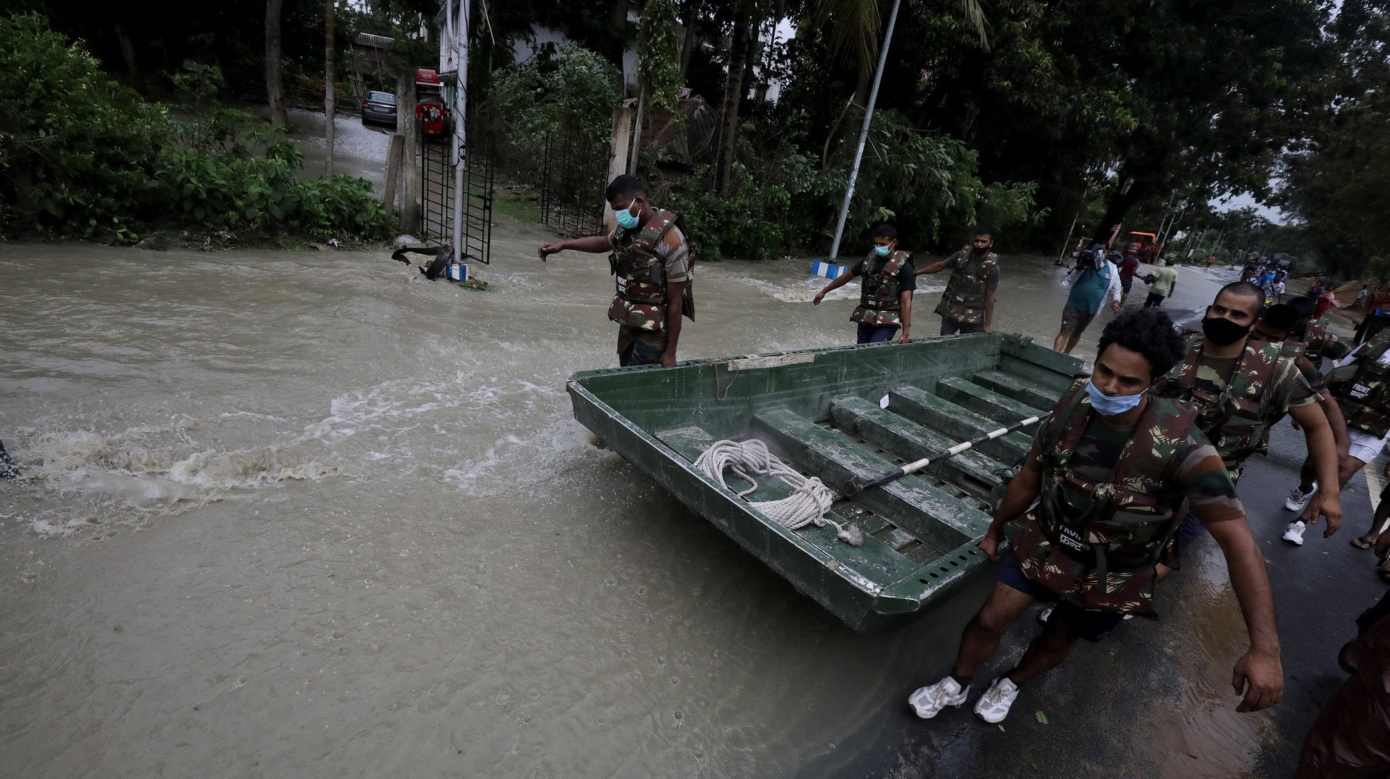 epa09228338 Indian Army personel carry a boat to rescue people amid floods as Cyclone Yaas makes landfall in Digha, near the Bay of Bengal, south of Kolkata, India, 26 May 2021. The Odisha and Bengal governments started the evacuation of at-risk areas, as Cyclone Yaas hits the eastern coast of India.  EPA/PIYAL ADHIKARY