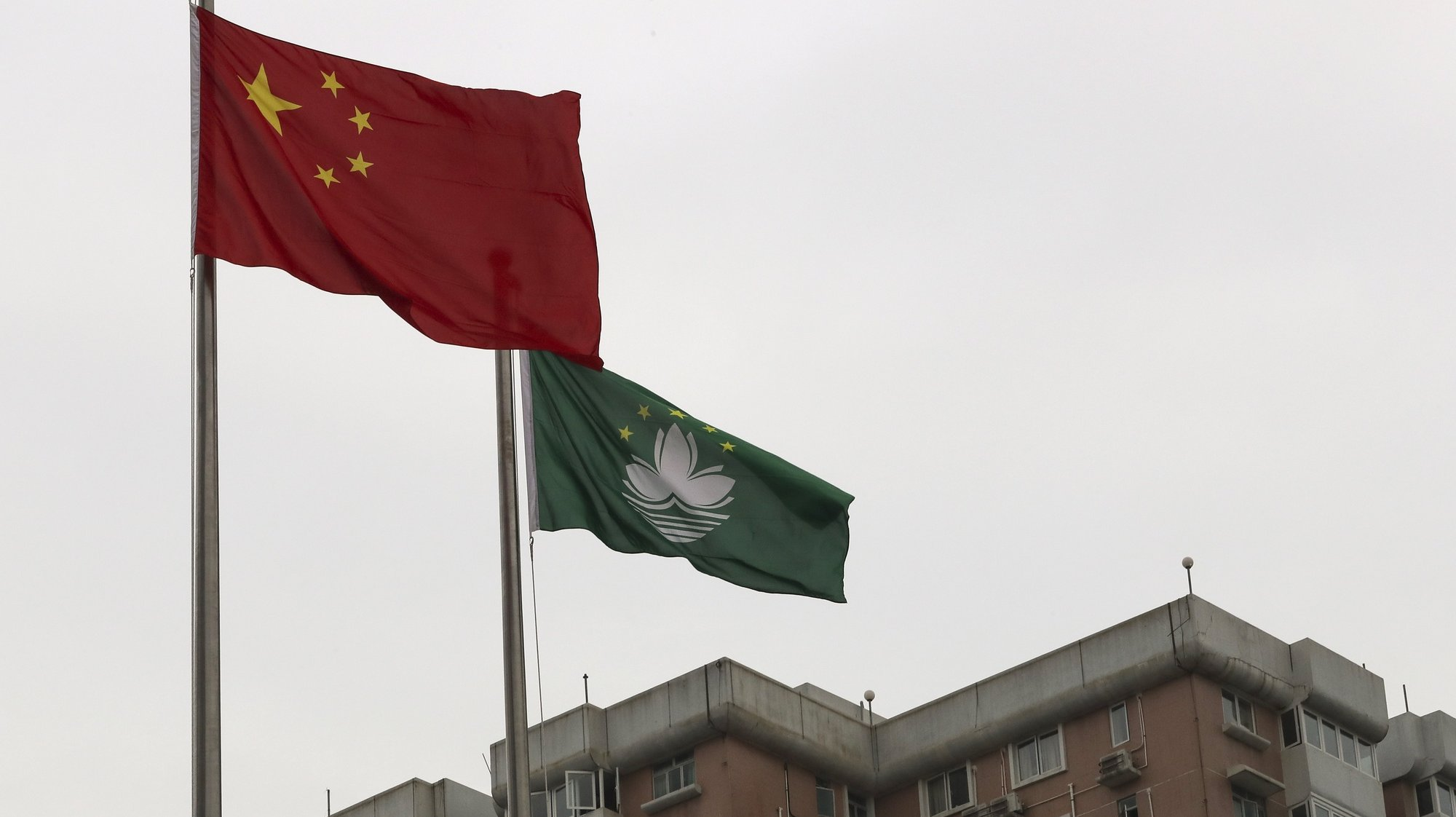 epa08082673 Chinese and Macao's flags wave during the flag-raising ceremony for Macao Special Administrative Region's (SAR) 20th anniversary at Lotus Flower Square in Macao, China, 20 December 2019. Macao had been a Portuguese colony until 1999 when it returned to Chinese rule under the 'one country, two systems' principle.  EPA/JOAO RELVAS