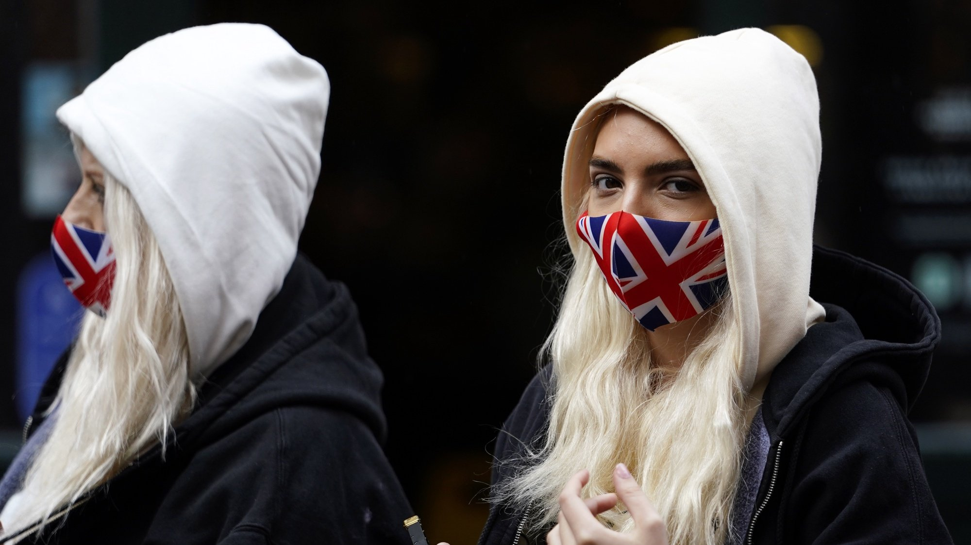 epa08747751 Women wearing Union Jack flag face masks walk in Central London, Britain, 15 October 2020. According to news reports, the UK government is set to impose further restrictions on London, as COVID-19 infections continue to rise. According to recent data from the Office for National Statistics (ONS), COVID-19 deaths in England have risen four fold over the last month.  EPA/WILL OLIVER