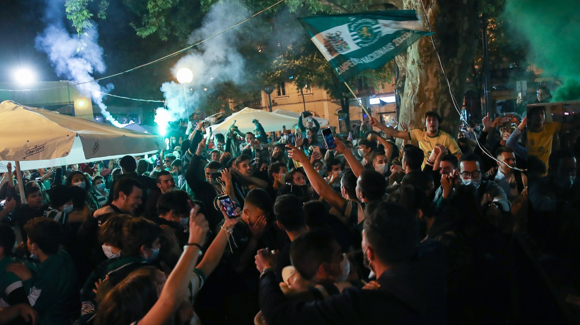 epa09192604 Sporting supporters celebrate the First League Soccer title at Republica square, in Coimbra, Portugal, 11 May 2021. Sporting of Lisbon defeated Boavista in their Portuguese First League soccer match conquering the First League trophy of the season 2020/2021, a trophy the team has been chasing since the season 2001/2002.  EPA/PAULO NOVAIS