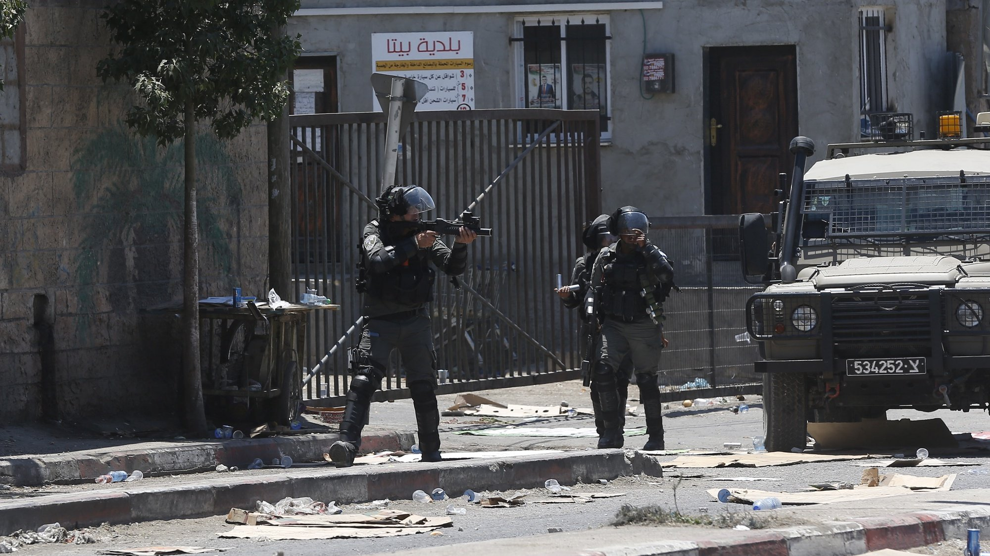 epa09282952 Israeli soldiers take position during clashes with Palestinian protesters after a protest against Israeli settlements at Beta village near the West Bank City of Nablus, 18 June 2021. According to Medical sources, 57 Palestinians were wounded during the clashes.  EPA/ALAA BADARNEH