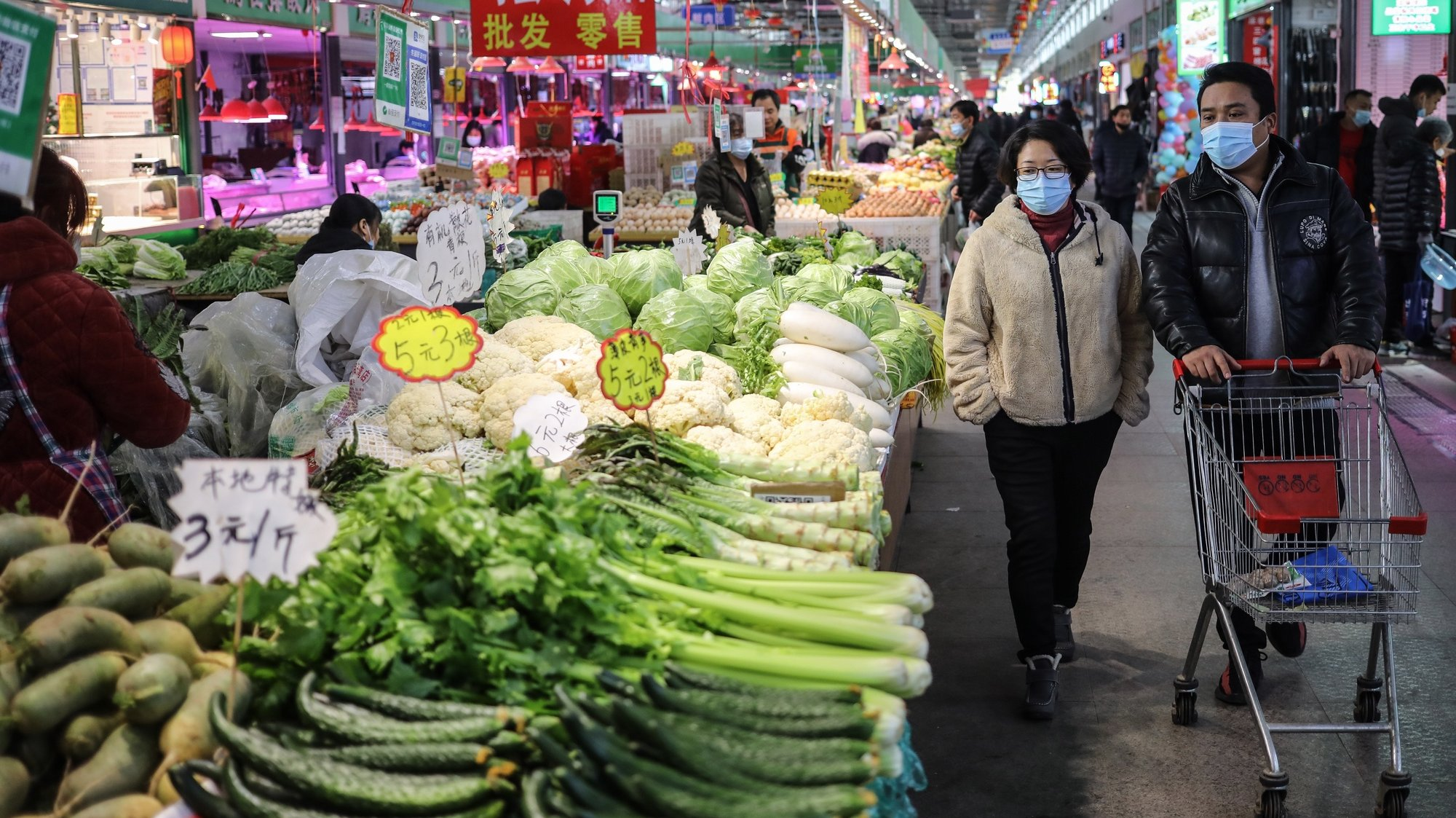 epa08871803 Consumers walk past vegetable stalls at a stall at a market in Beijing, China, 09 December 2020. According to the National Bureau of Statistics, China's Consumer Price Index (CPI), which is a main gauge of inflation, down 0.5 percent year-on-year in November 2020 that posted the first year-on-year drop in 11 years.  EPA/WU HONG