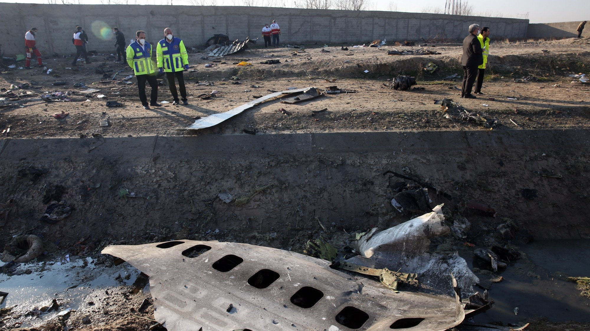 epa08619656 (FILE) - Officials stand near the wreckage after an Ukraine International Airlines Boeing 737-800 carrying 176 people crashed near Imam Khomeini Airport in Tehran, killing everyone on board, in Shahriar, Iran, 08 January 2020 (reissued 23 August 2020). Investigators in Iran said that the cockpit black box recorded a conversation between the pilots just after a missile hit the Ukrainian passenger jet in January 2019. The Beoing 737 was mistakenly shot down by Iran, killing 176 passengers on board.  EPA/ABEDIN TAHERKENAREH *** Local Caption *** 56222509