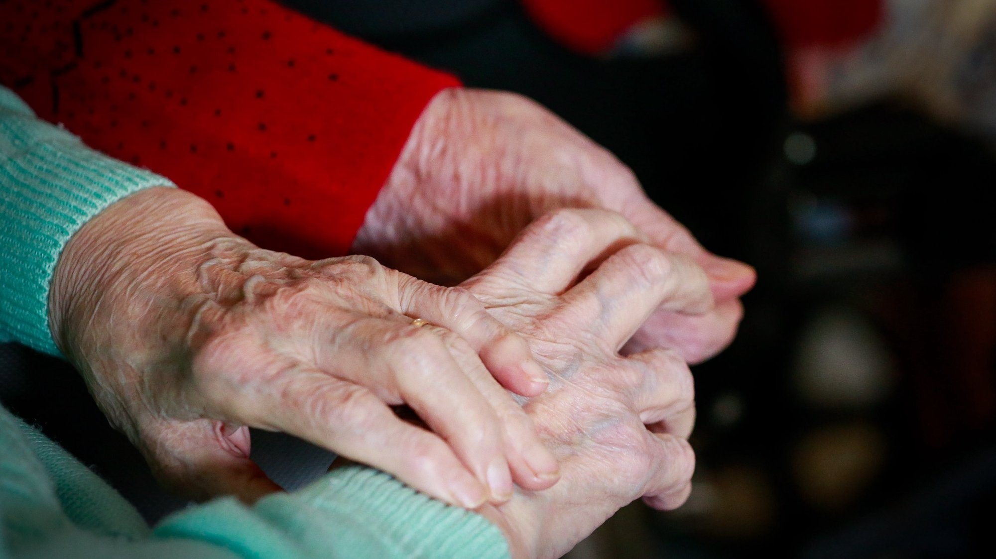 epa08786229 Two friends resident hold each other hands while they watch TV show at the 'Notre Dame De Bonne Esperance' nursing home in Chatelet, Belgium, 30 October 2020. Due to COVID-19, residents of the nursing home are not allowed to leave among the measures taken to protect residents from the spread of coronavirus.  EPA/STEPHANIE LECOCQ