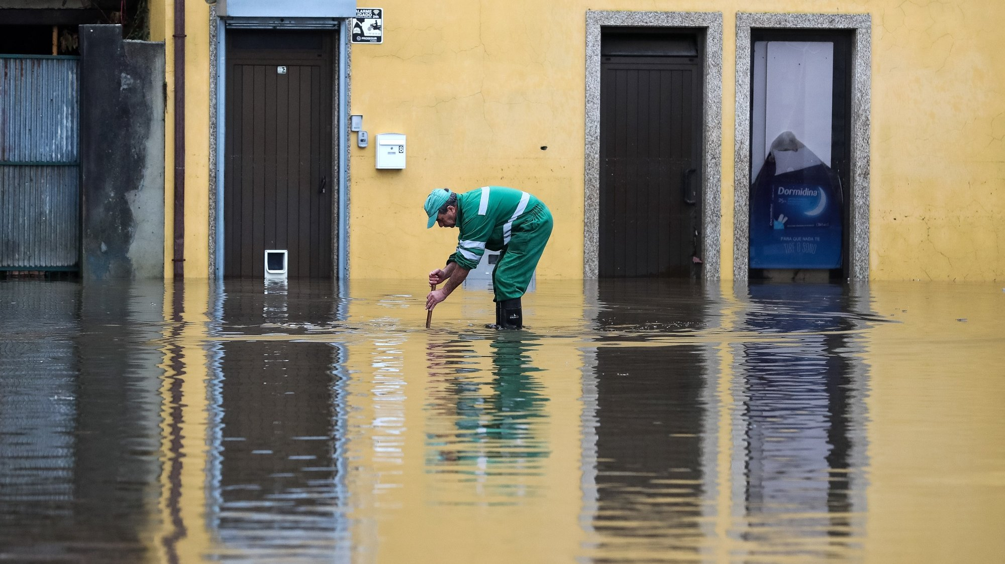 Um funcionário camarário limpa uma sargeta na zona ribeirnha da cidade de Águeda, que foi inundada pela subida da água do rio Águeda devido à chuva forte provocada pela depressão Elsa, em Águeda, 20 de dezembro de 2019. PAULO NOVAIS/LUSA