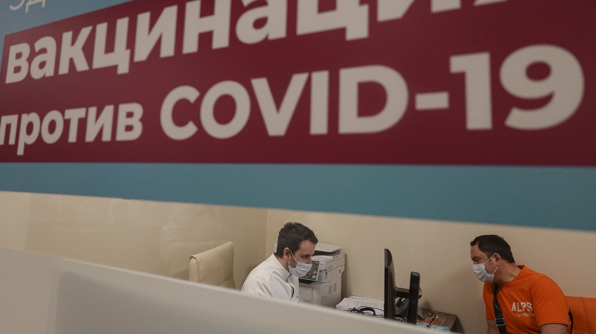 epa08983839 Medics work behind the sign reading 'Vaccination against COVID-19 is carried out here' at the vaccination point at the Columbus shopping mall in Moscow, Russia, 03 February 2021. Russia began a program for mass vaccination against COVID-19 disease, caused by SARS-CoV-2 coronavirus, using the Sputnik V vaccine from January 19. About 8.2 million doses of coronavirus vaccines have been released in Russia. More than 420 thousand people were vaccinated in Moscow. The number of vaccination stations in Russia is growing rapidly: in about a week it increased almost one and a half times - from 2.25 thousand to 3.1 thousand.  EPA/SERGEI ILNITSKY