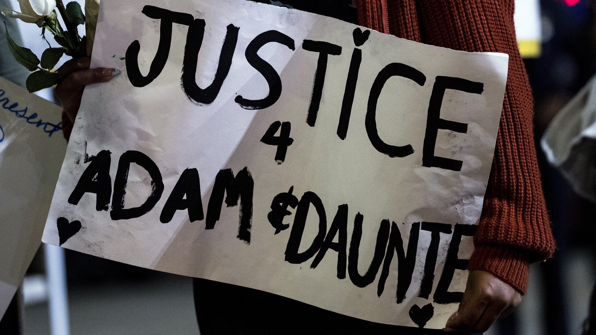 epa09144487 A demonstrator holds a poster reading 'Justice for Adam and Daunte' during a candlelight vigil and rally for Daunte Wright and Adam Toledo at Leimert Park Plaza, in Los Angeles, California, USA, 18 April 2021. 20 year old Daunte Demetrius Wright was fatally shot by police officer Kimberly Ann Potter in Brooklyn Center, Minnesota on April 11, 2021. On March 29, 2021, 13 year old Adam Toledo was shot and killed by police officer Eric Stillman in the Little Village neighborhood on the West Side of Chicago on March 29, 2021.  EPA/ETIENNE LAURENT