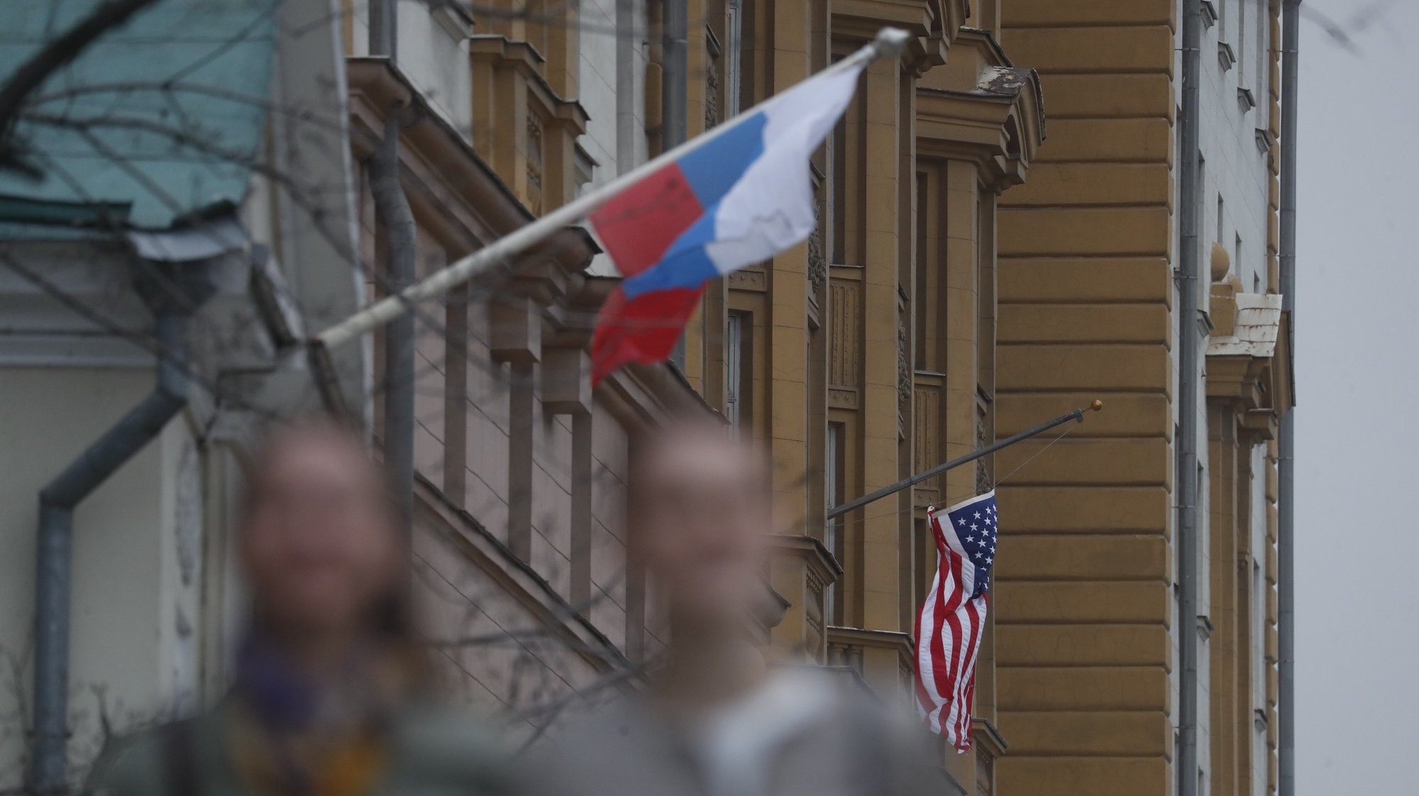epa09137644 A Russian flag (L) next to the US embassy building in Moscow, Russia, 15 April 2021. Tensions have escalated between the US and Russia following the new sanctions announced by the United States against Russia.  EPA/MAXIM SHIPENKOV
