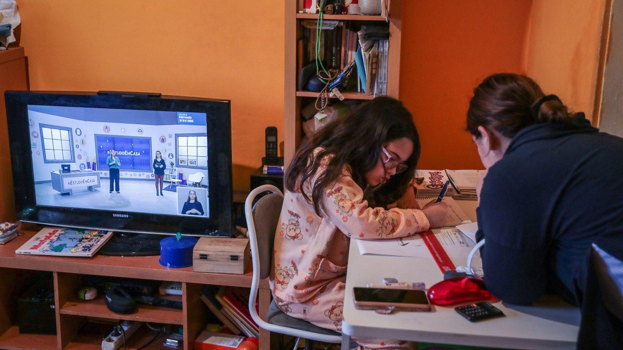 Daniela de 09 anos é auxiliada pela sua mãe, Ana Costa, enquanto assiste às aulas pela televisão, na Amadora, 20 de abril de 2020. Mais de 850 mil alunos do ensino básico contam a partir de hoje e durante o terceiro período, entre as 9:00 e as 17:30, mais de uma centena de professores vão dar aulas de apoio através da televisão, e vão aprender com a ajuda de mais de uma centena professores à distância devido à pandemia de covid-19. O Governo decretou o estado de emergência a 19 de março, que já foi prorrogado duas vezes, estando previsto agora o seu fim a 02 de maio. TIAGO PETINGA/LUSA