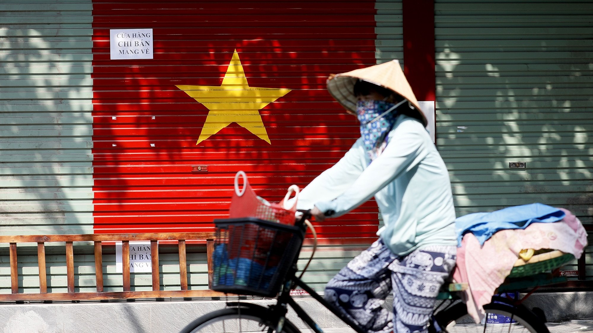 epa09352987 A woman wearing a face mask rides bicycle at a street in Hanoi, Vietnam, 19 July 2021. Vietnam tightened restrictions in 19 provinces, after nearly 6,000 new COVID-19 cases were reported in one day in the country.  EPA/LUONG THAI LINH